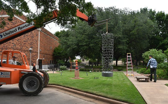 Joe Barrington, left, and Suguru Hiraide prepare to instal a sculpture by Jim Robertson of Trinity, Texas. The Kemp Center for the Arts received 12 new sculptures for its outdoor sculpture garden.