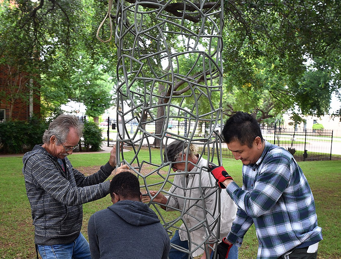 "Artist Jim Robertson, left, gets some help from Joe Barrington, Suguru Hairaide and Ferdine LaBlanc as they position his steel and enamel sculpture, ""Column"", at the Kemp Center for the Arts Sculpture Garden Friday."