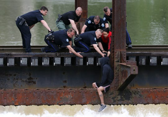 Officers of the Zanesville Police Department help a man off the railroad bridge near the Y bridge Friday afternoon. The man, who had threatened to jump, was safely escorted to a waiting ambulance.