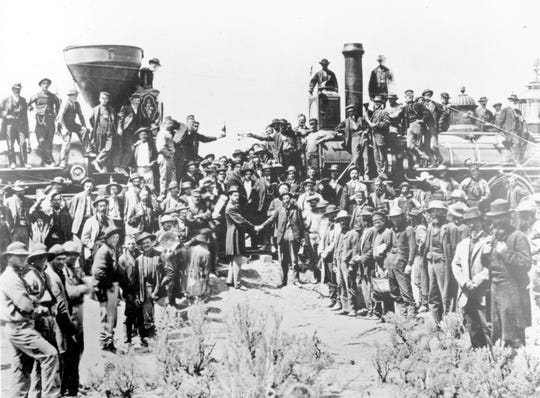 In this May 10, 1869, file photo, provided by the Union Pacific, railroad officials and employees celebrate the completion of the first railroad transcontinental link in Promontory, Utah. The Union Pacific's Locomotive No. 119, right, and Central Pacific's Jupiter edged forward over the golden spike that marked the joining of the nation by rail.