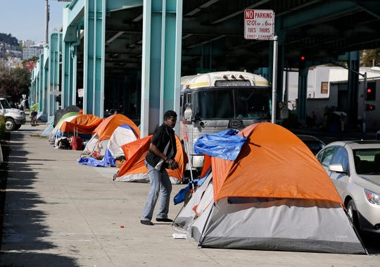 In this 2016 file photo, a man stands outside his tent on Division Street in San Francisco. California Gov. Gavin Newsom, outlined his plans in his proposed budget to spend $1.75 billion on housing in a state that is woefully short on units and $500 million on homelessness. In Newsom's first 100 days as governor, he's placed a moratorium on the death penalty, set aggressive goals to increase housing and battled with the Trump administration on immigration.