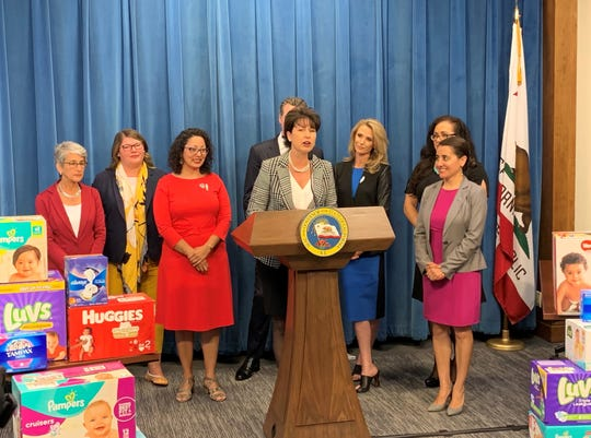 California state senator Connie Leyva, at the lecturn, joins Gov. Gavin Newsom and his wife Jennifer Siebel Newsom at the governor's recent press conference to announced a revised budget that features a number of proposals aimed at young families and children.