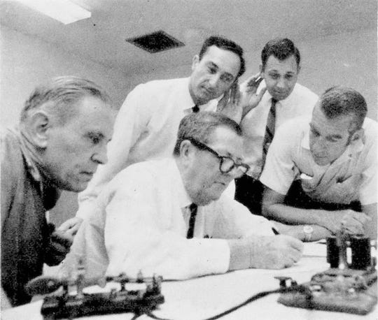 In this May 10, 1969, file photo, Associated Press White House correspondents Doug Cornell, left, and Frank Cormier, right, watch as Western Union officials receive a direct wire Morse message in Miami from Promontory, Utah. The message was a duplicate of the one sent 100 years earlier after the completion of the first railroad transcontinental link. Another message was sent to President Nixon nearby in Key Biscayne, Fla., like the one sent to President Grant 100 years earlier.