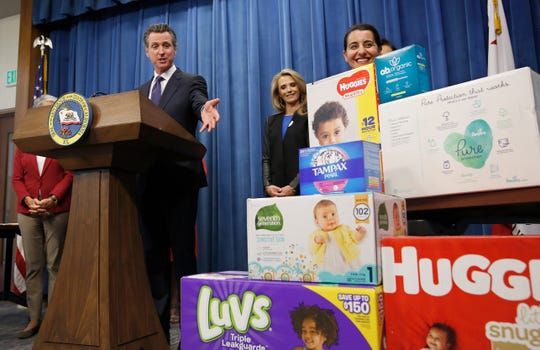 California Gov. Gavin Newsom gestures towards boxes of tampons and diapers after proposing to eliminate from the state sales tax on such products in his upcoming state budget during a news conference, Tuesday, May 7, in Sacramento. The tax cuts are part of a Parents Agenda Newsom is pursuing. He was accompanied by his wife, first partner Jennifer Siebel Newsom, center, Southern California Democratic Assemblywoman Monique Limon is at right.