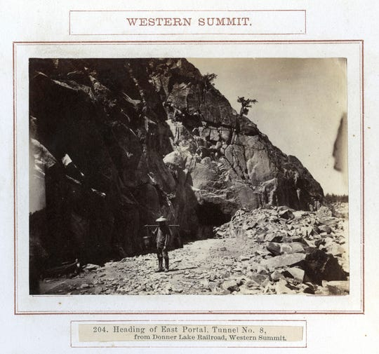 In this photo taken between 1862 and 1869, a Chinese laborer works at a tunnel heading above Donner Lake on the western summit of the Transcontinental Railroad in Northern California. Members of the Chinese Railroad Workers Descendants Association are gathering in Utah in May 2019 to commemorate the 150th anniversary of the railroad's completion