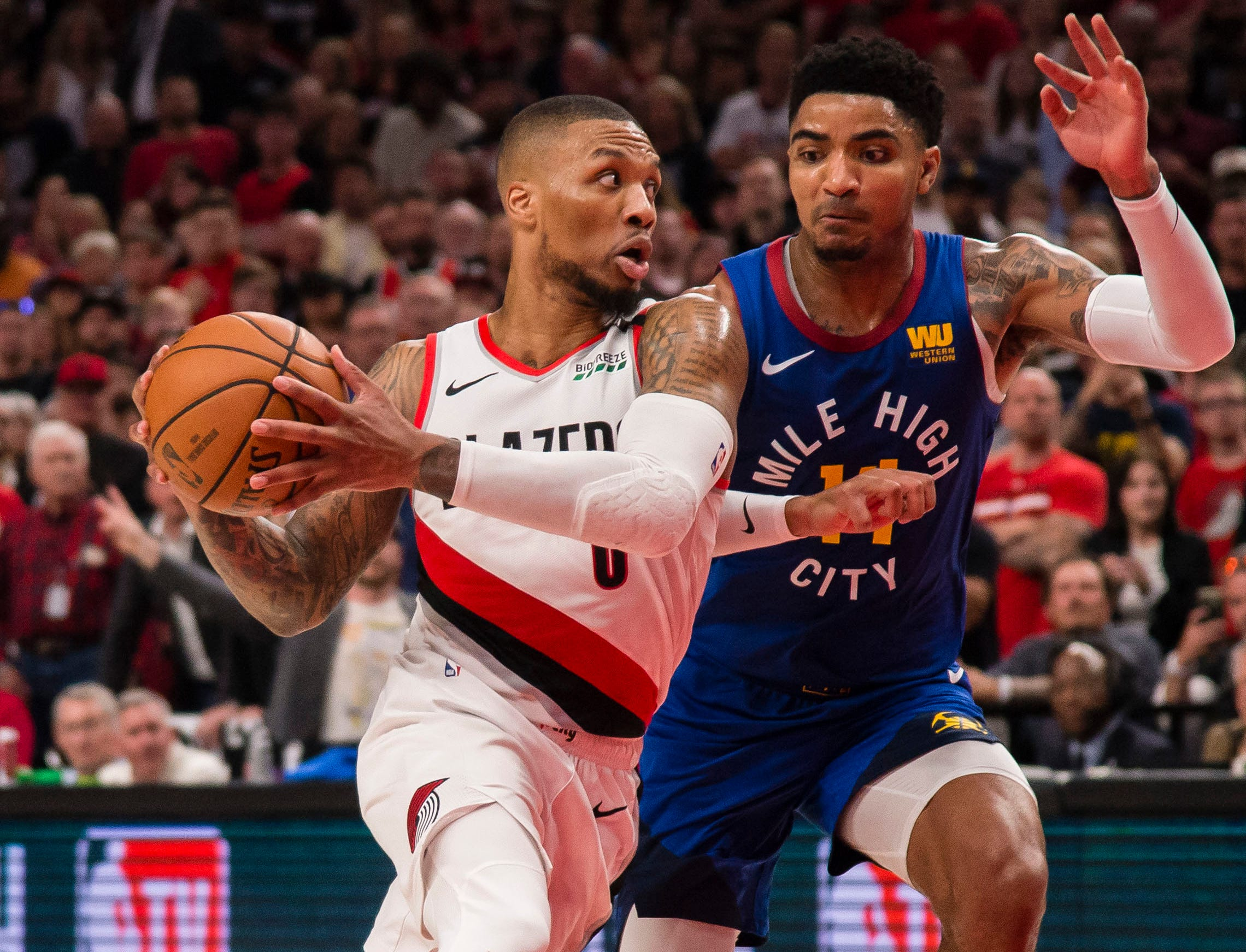 May 9: Blazers guard Damian Lillard (0) drives against Nuggets defender Gary Harris (14) during Game 6 in Portland.
