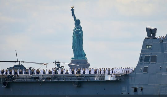 The USS Arlington, from Norfolk, Va., a San Antonio-class amphibious transport dock with several hundred Marines from Camp Lejeune, N.C., arrives on the Hudson River to kickoff 2018 Fleet Week New York, Wednesday May 23, 2018, in New York.