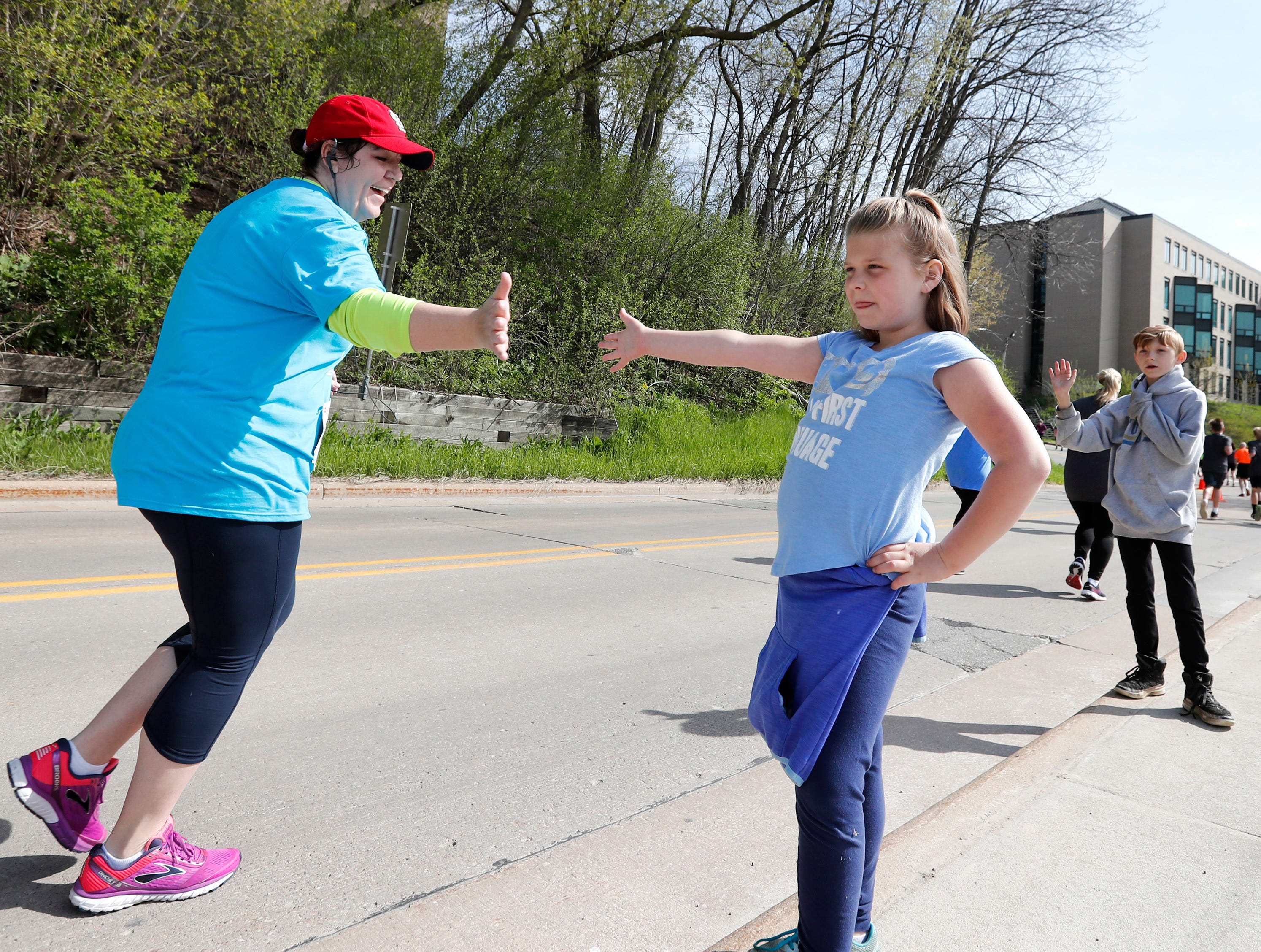 Mikayla Holschbach, 8, and her brother Malachi high five runners while waiting for their mother during the Sole Burner 5K Walk-Run Saturday, May 11, 2019, in Appleton, Wis. Danny Damiani/USA TODAY NETWORK-Wisconsin