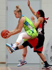 Gabbi Ortiz of the Wisconsin Glo fends off Morgan Neenly of the Flint Monarchs on Friday at Menominee Nation Arena.