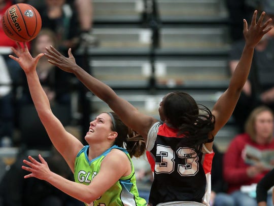 The Wisconsin Glo's Steph Kostowicz, left, drives to the basket against the Flint Monarchs's Brandie Baker at Menominee Nation Arena on Friday in Oshkosh.