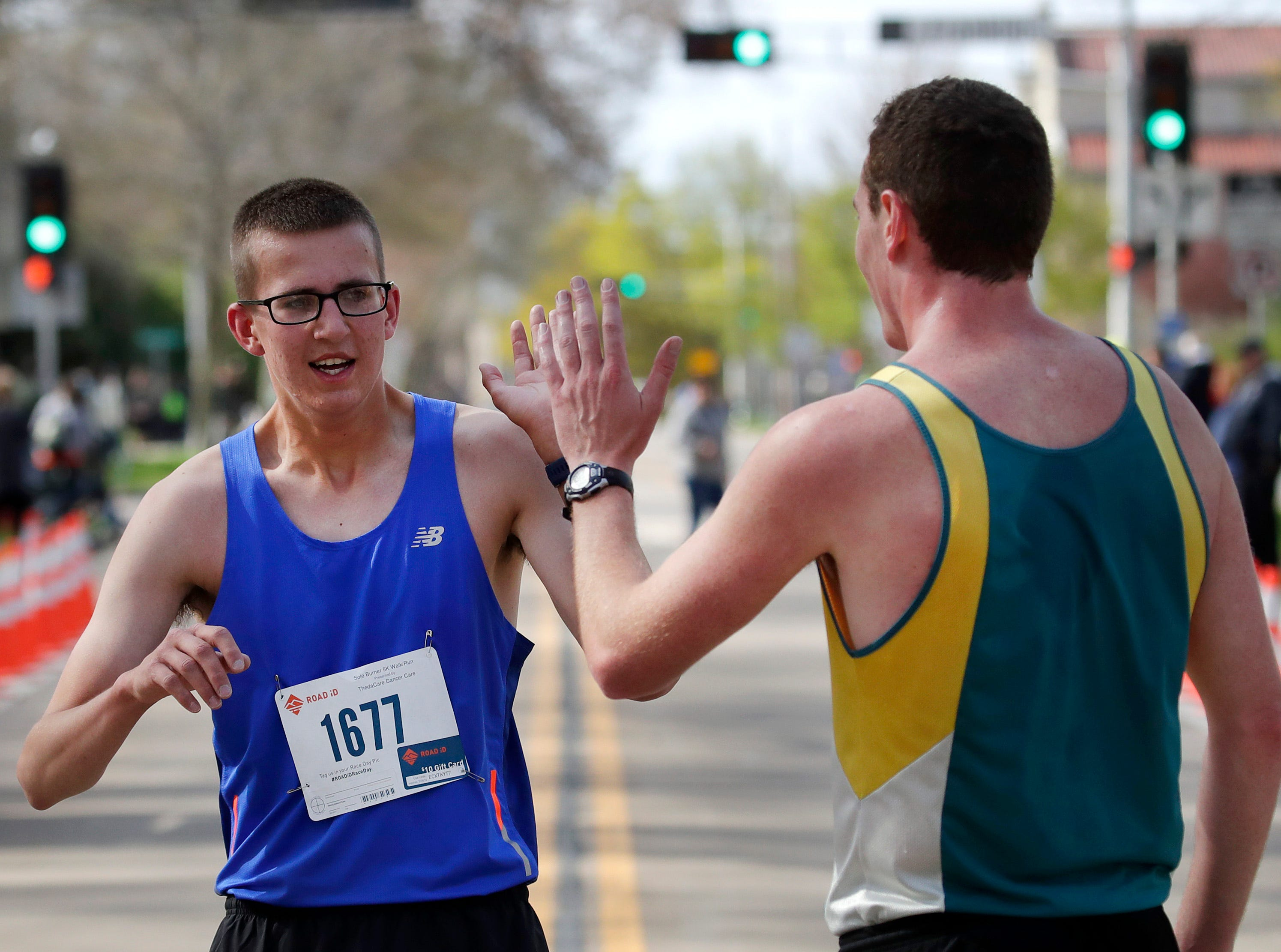 Duncan Tjader high fives Logan Jadin after crossing the finish line during the Sole Burner 5K Walk-Run Saturday, May 11, 2019, in Appleton, Wis. Danny Damiani/USA TODAY NETWORK-Wisconsin