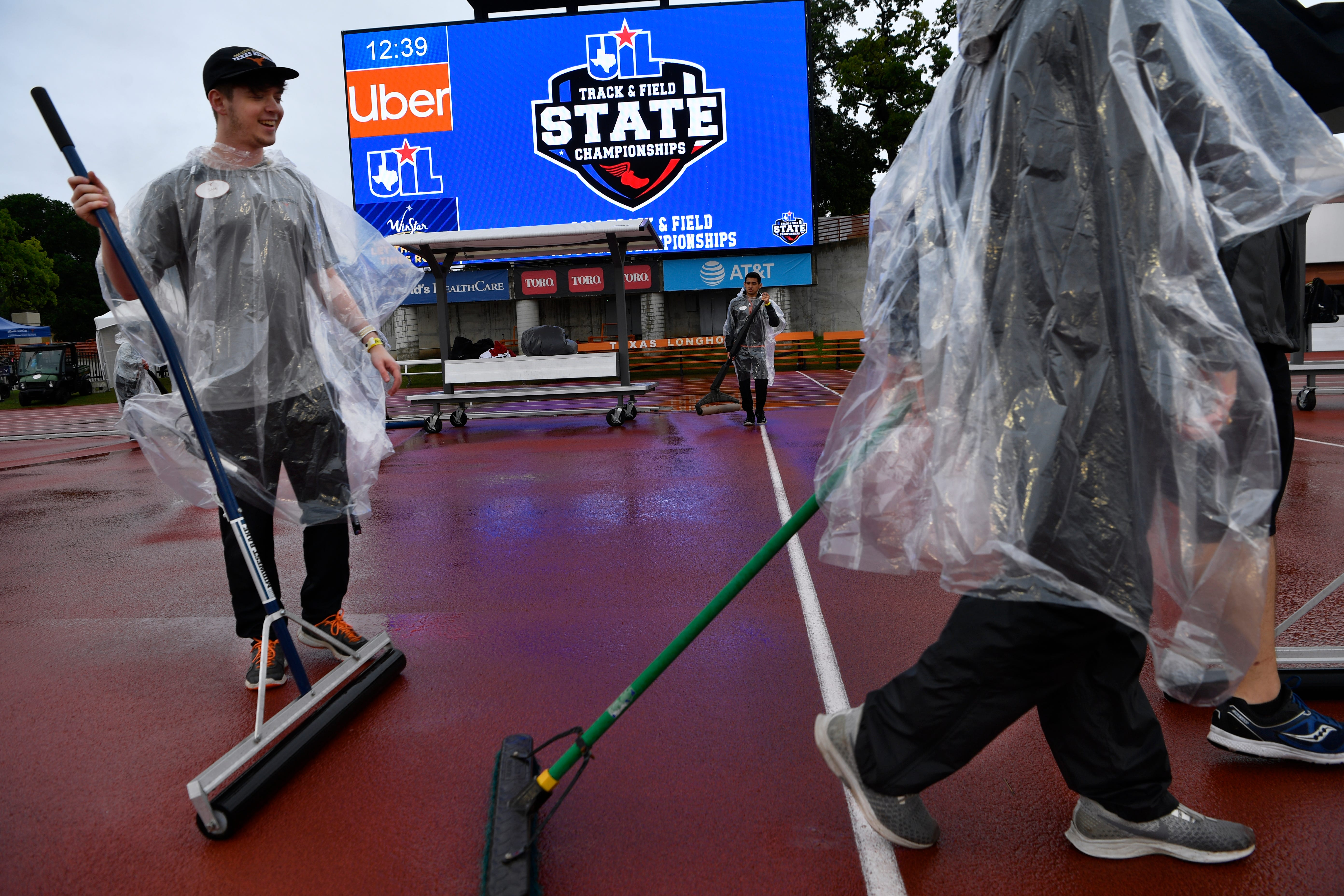 Sam Bellessa (left) and other University of Texas students, sweep the rainwater off the track at Mike A. Myers Stadium Saturday May 11, 2019. Rain delayed the UIL State Track & Field Championships in Austin for over an hour.