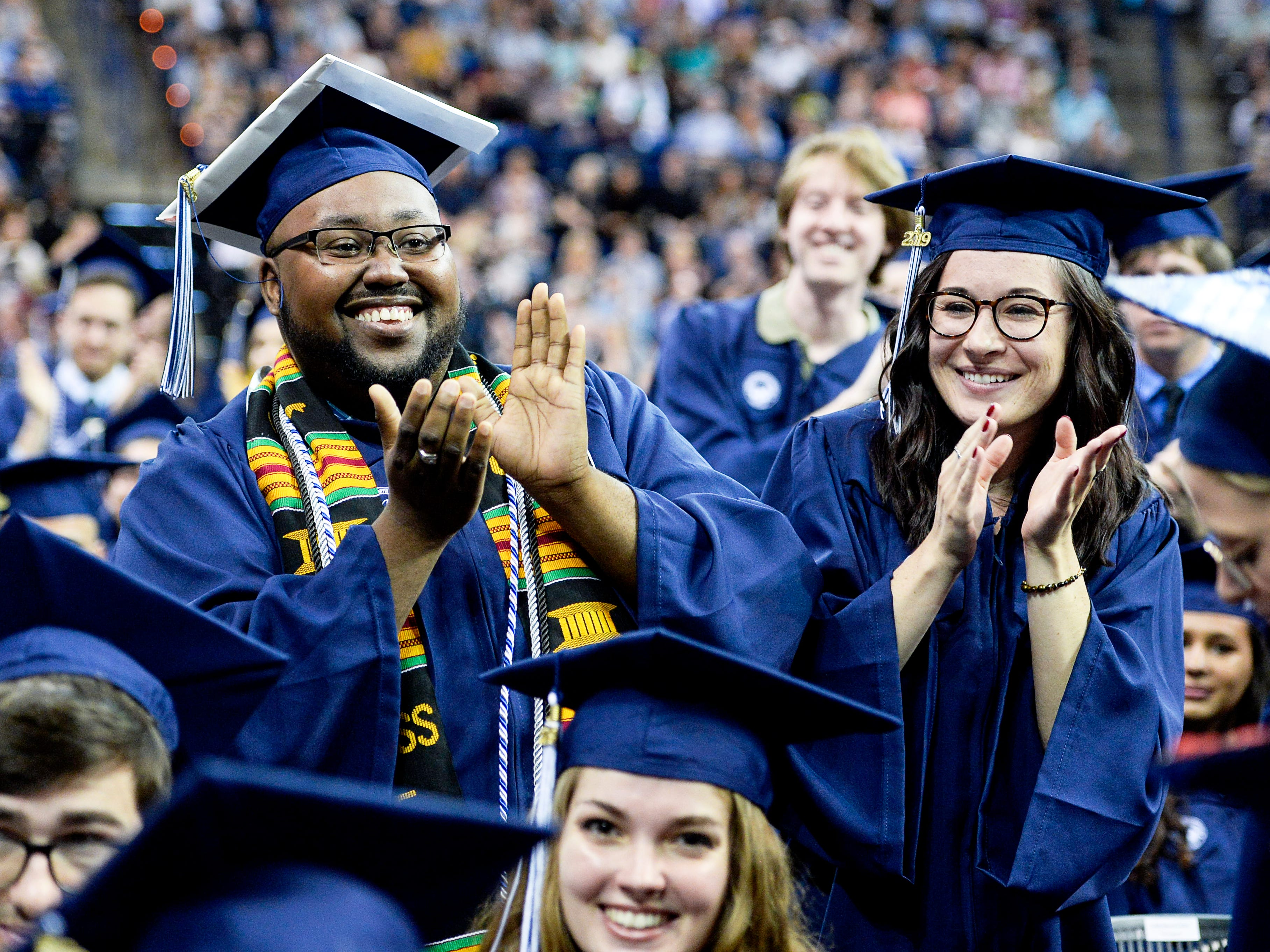 UNC Asheville graduates clap as the UNC Board of Governors Award for Excellence in Teaching is announced during commencement May 11, 2019.
