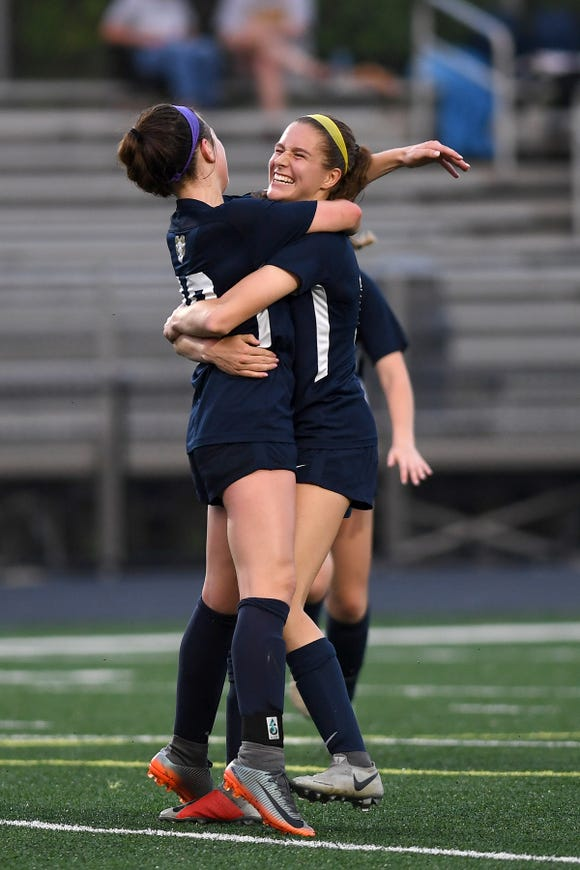 Roberson's Isabelle Ingle hugs Maddie Luckett after she scored a goal during their NCHSAA 3A playoff game at Roberson High School on May 10, 2019. Roberson defeated Mount Tabor 3-0 to advance.