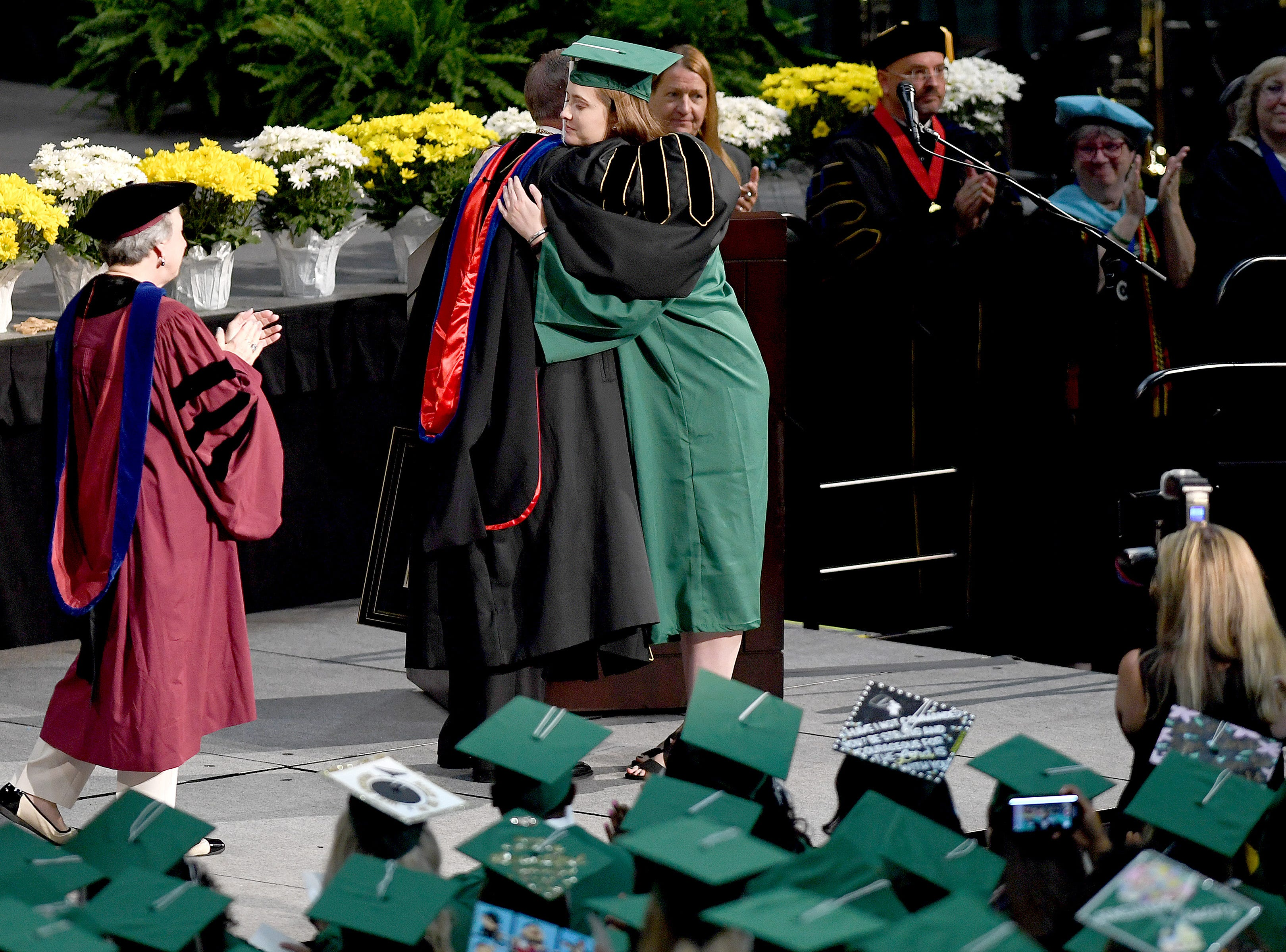 UNC Charlotte graduate Emily Houpt hugs chancellor Philip Dubois as she is honored and given her B.A in International Studies during the University's Commencement ceremony for the College of Liberal Arts and Sciences in Charlotte on May 11, 2019. Houpt was injured in the April 30 shooting at the university.
