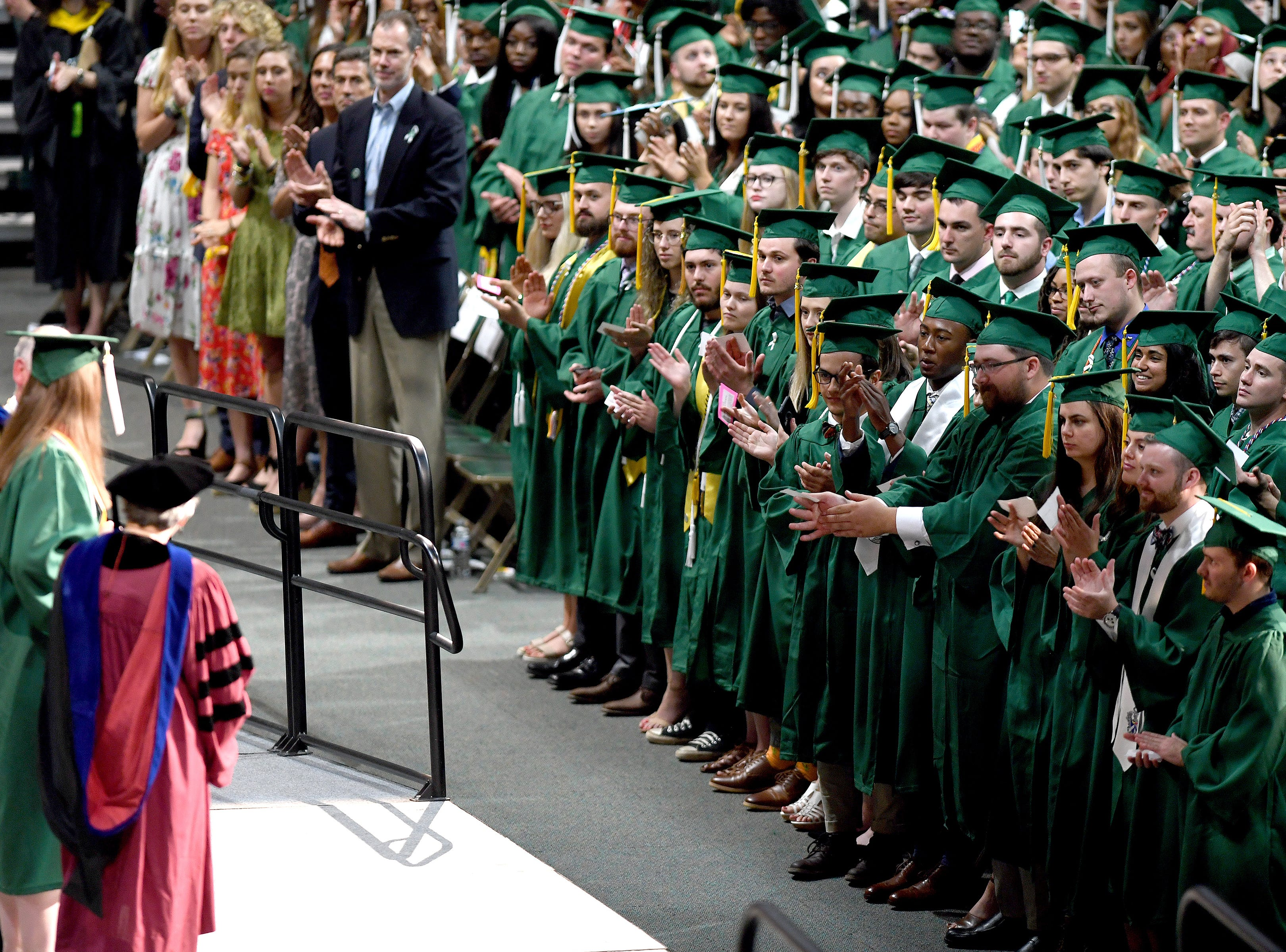 UNC Charlotte graduates applaud Emily Houpt as she is honored and receives her B.A in International Studies during the University's Commencement ceremony for the College of Liberal Arts and Sciences in Charlotte on May 11, 2019. Houpt was injured in the April 30 shooting at the university.
