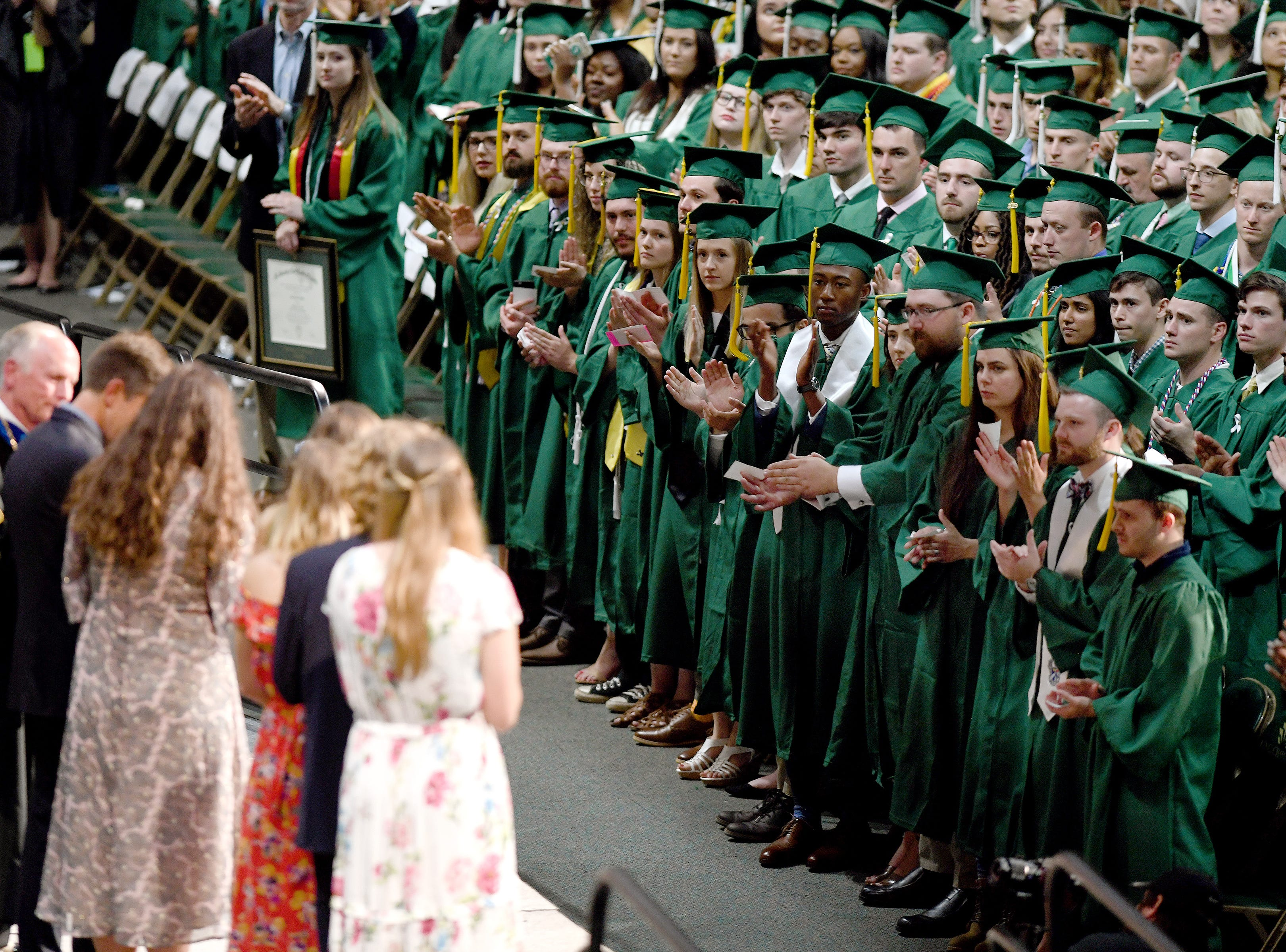 UNC Charlotte graduates applaud and give a standing ovation to Riley Howell's family as he is honored and Howell is awarded a B.A. in Memoriam during the University's Commencement ceremony for the College of Liberal Arts and Sciences in Charlotte on May 11, 2019. Riley Howell was killed in the April 30 shooting at the university.