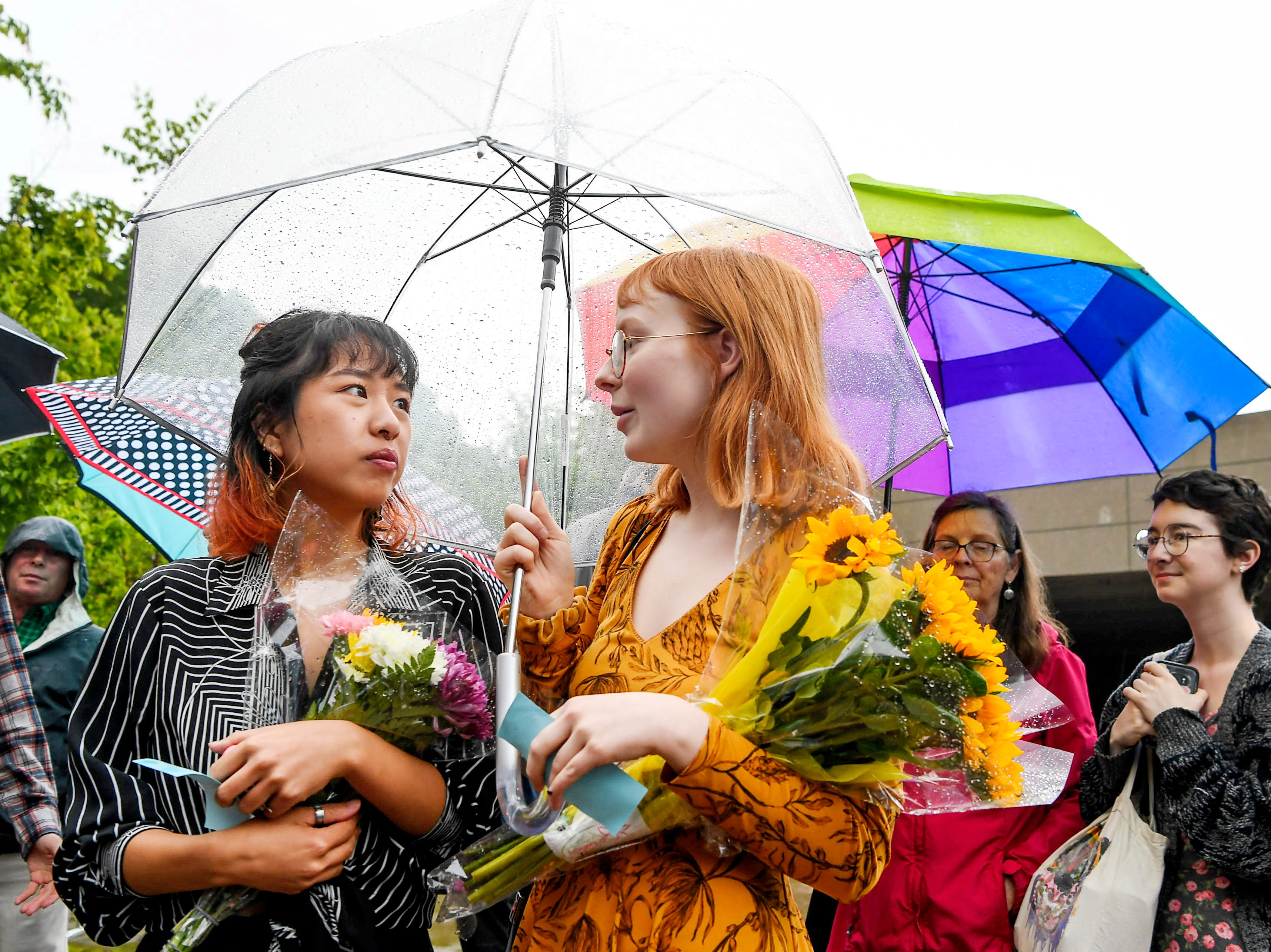 Yen Nguyen, left, and Riley Fair, wait in the rain with flowers for their graduating friends before the UNC Asheville commencement ceremony May 11, 2019.