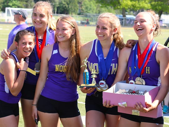 North Kitsap's Raelee Moore (right) celebrated her 18th birthday with teammates Saturday at the Olympic League 2A track and field championships at North Kitsap.