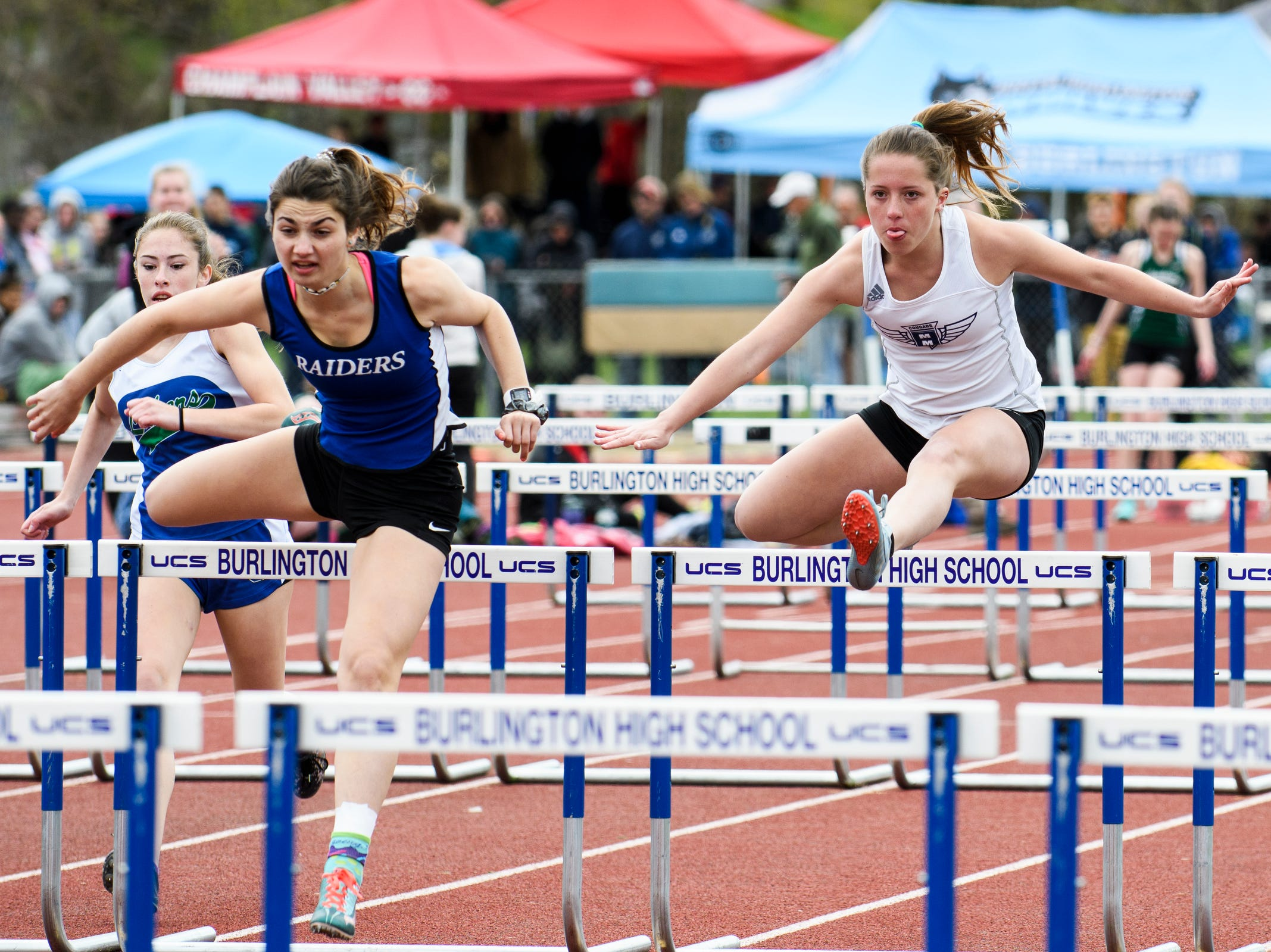 MMU's Ava Esmay and U-32's Julia Oliver, left, compete in the 100m hurdles during the Burlington Invitational high school track and field meet at Buck Hard Field on Saturday May 11, 2019 in Burlington, Vermont.