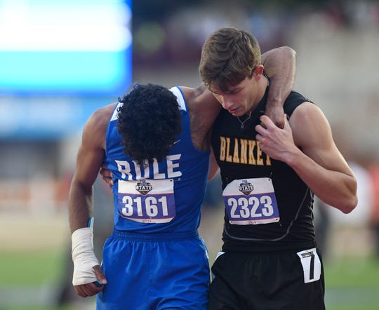 Rule's Chase Thompson, left, is helped by Blanket's Logan Wheeler after suffering an injury during the 1A boys 100 meter dash during the UIL State Track and Field meet, Friday, May 10, 2019, in Austin.