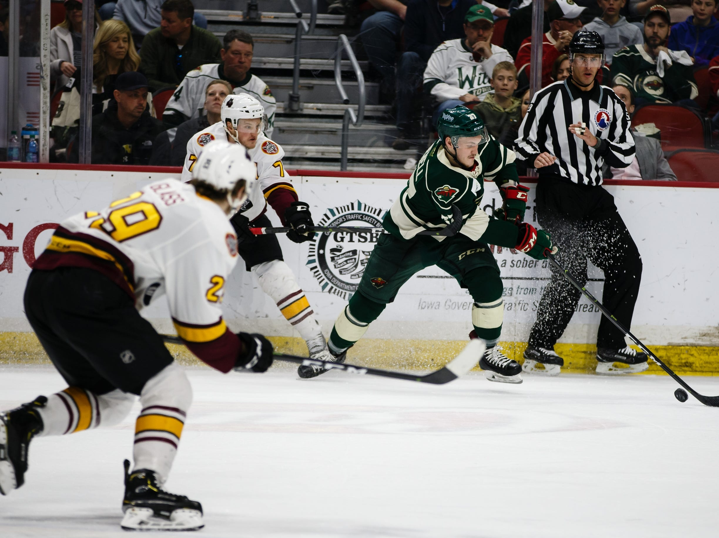 The Iowa Wild's Brennan Menell tries to get away from the Chicago Wolves Daniel Carr during the second period of their Calder Cup playoff hockey game on Friday, May 10, 2019, in Des Moines.