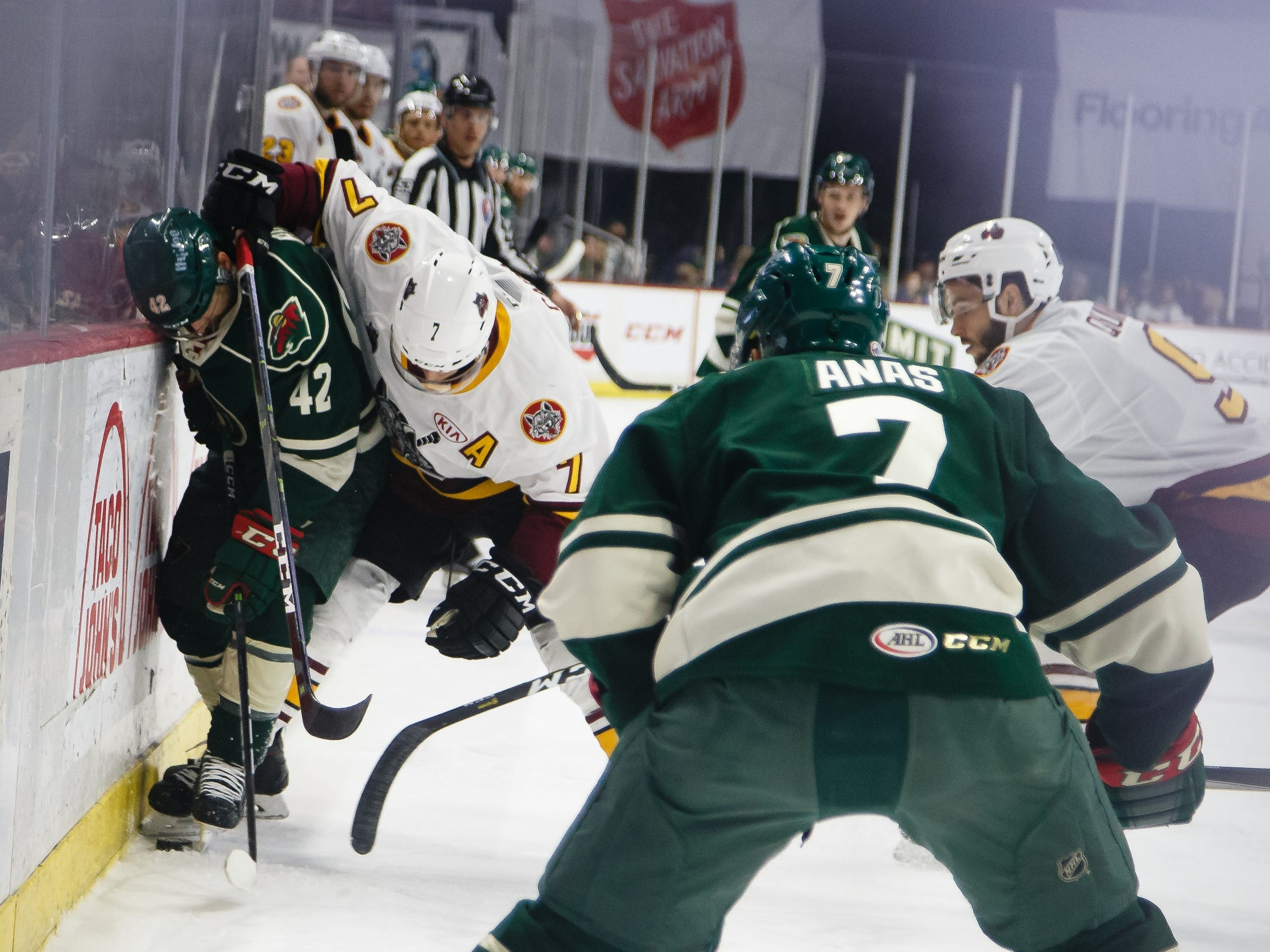 The Iowa Wild's Kyle Rau, left, fights for the puck with the Chicago Wolves Daniel Carr during their Calder Cup playoff hockey game against the Chicago Wolves on Friday, May 10, 2019, in Des Moines.