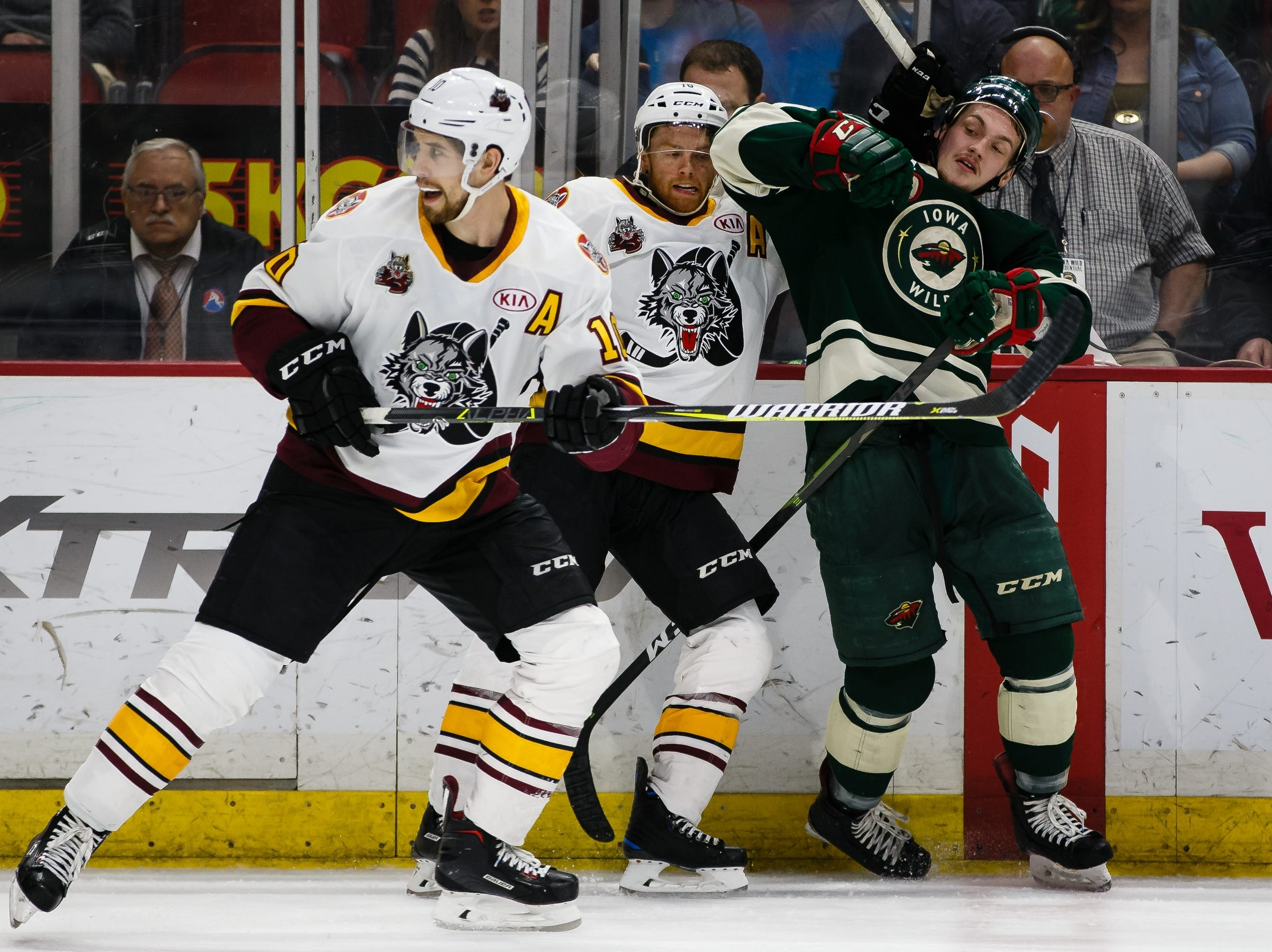 The Iowa Wild's Brennan Menell gets tangled up with the Chicago Wolves' T.J. Tynan during the second period of their Calder Cup playoff hockey game on Friday, May 10, 2019, in Des Moines.