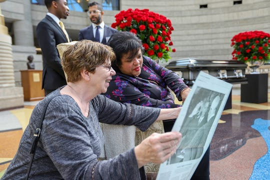 Sheryl James looks over the Detroit Free Press' memorial section with Debbie Keith that reflects on Sixth Circuit Court Judge Damon Keith's life at his  public visitation at the Charles H. Wright Museum of African American History in Detroit on Saturday, May 11, 2019.