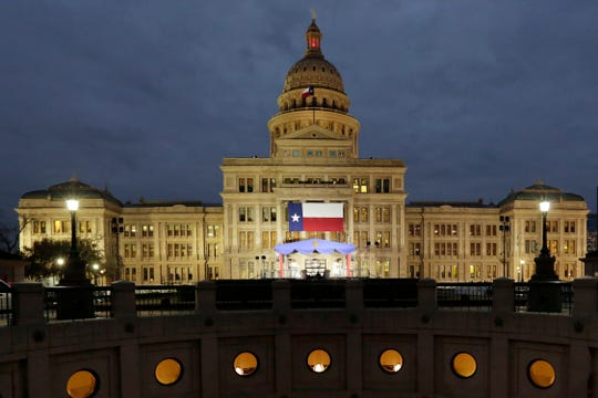 In this Jan. 14, 2019 file photo, a large Texas flag hangs from the Texas State Capitol as workers prepare the grounds for inauguration ceremonies in Austin, Texas.