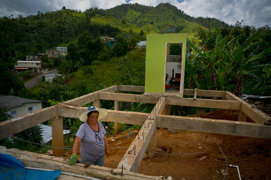 In this Sept. 8, 2018 file photo, Alma Morales Rosario poses for a portrait between the beams of her home being rebuilt after it was destroyed by Hurricane Maria a year earlier in the San Lorenzo neighborhood of Morovis, Puerto Rico.