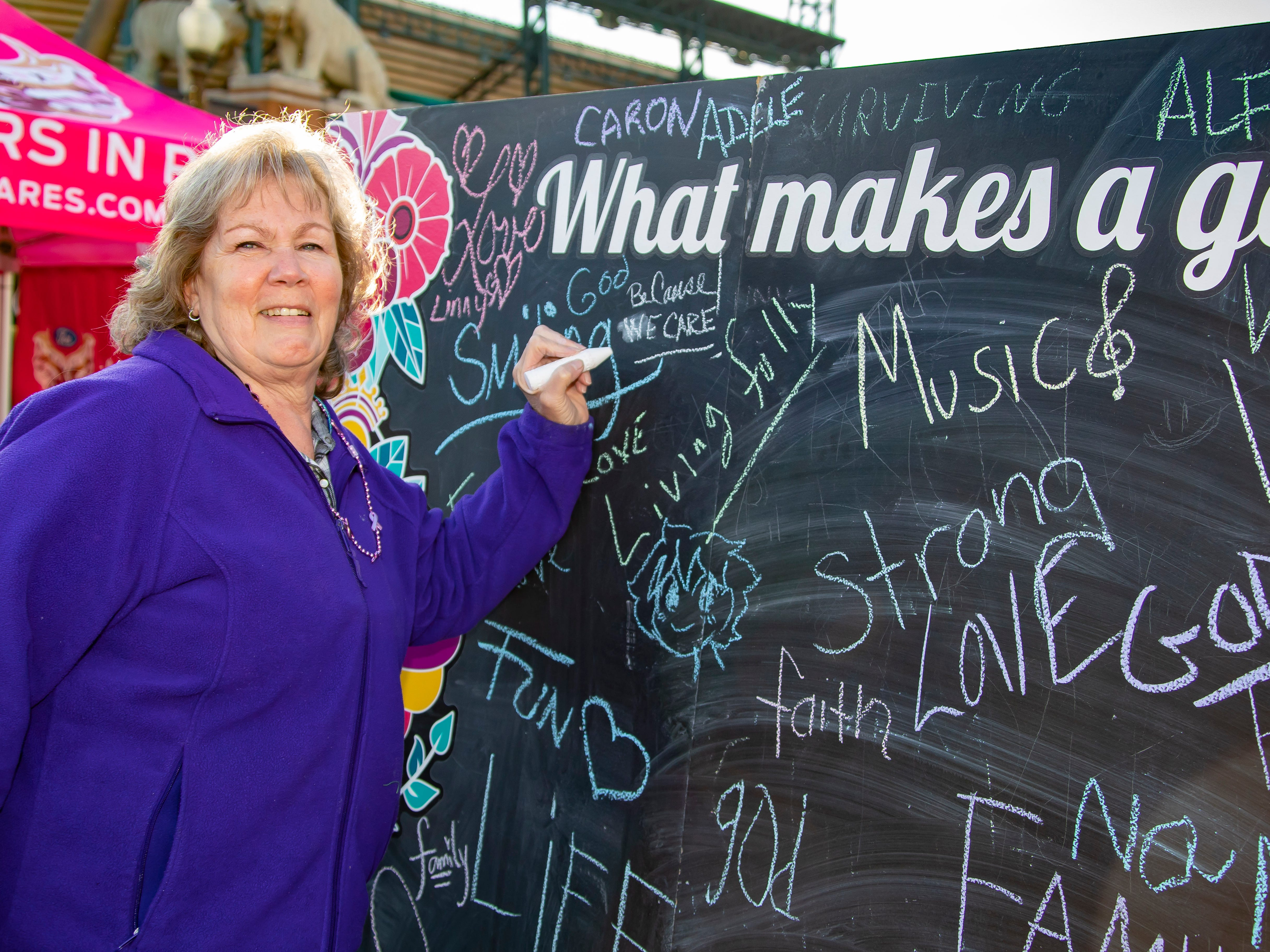 Diane McDonald signs the memory chalk board during the Susan G. Komen Race for the Cure at Comerica Park in Detroit Michigan. (Photo by Dave Reginek-Special to Detroit News)