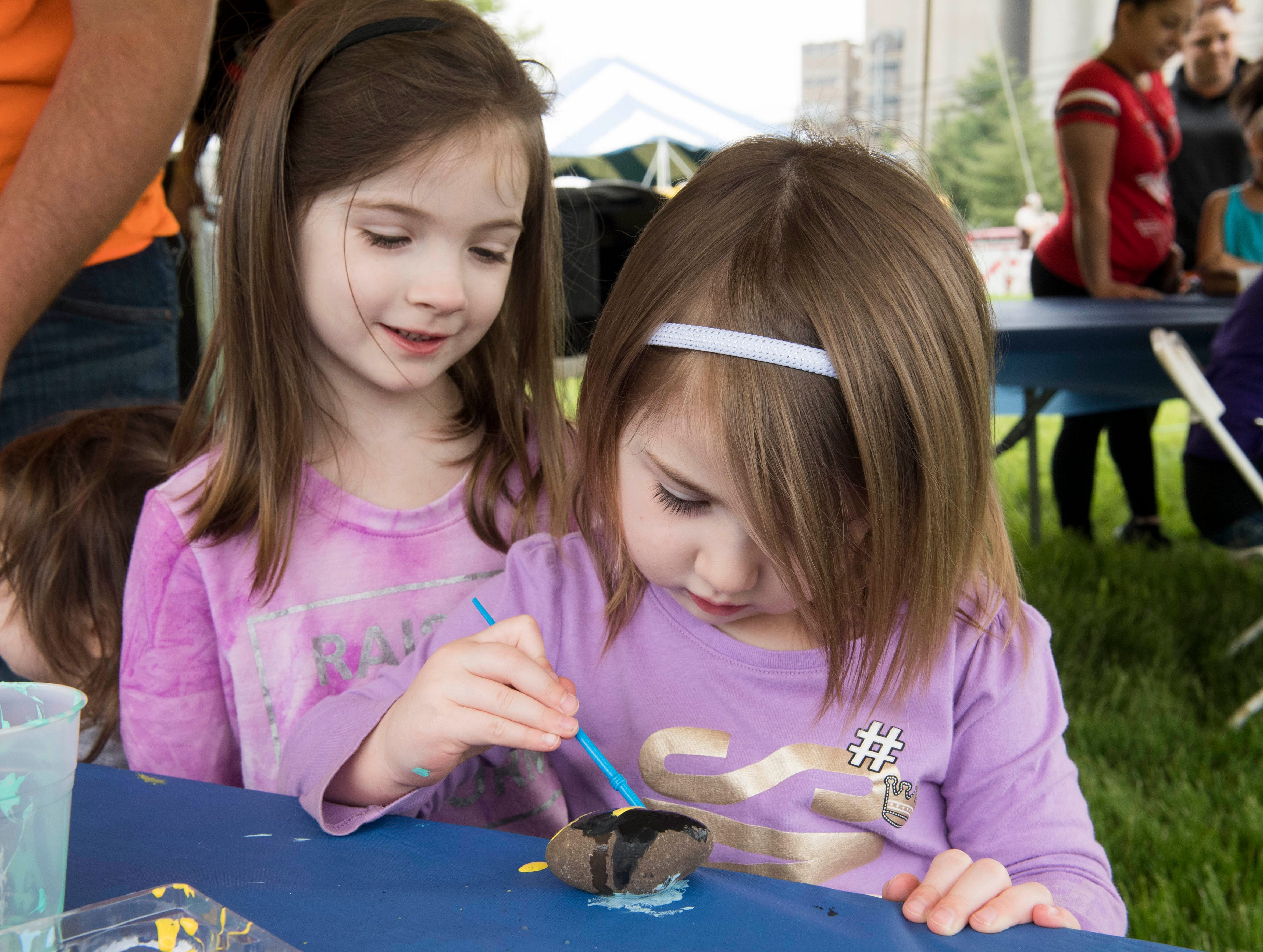 Julia West, 5, watches her sister Ella, 3, paint a rock during the 2019 Spirit Fest Saturday, May 11, 2019. Spirit Fest is a day of fun and activities that benefits the Spirit Medical Fund which raises money for the Evansville Animal Care and Control shelter.