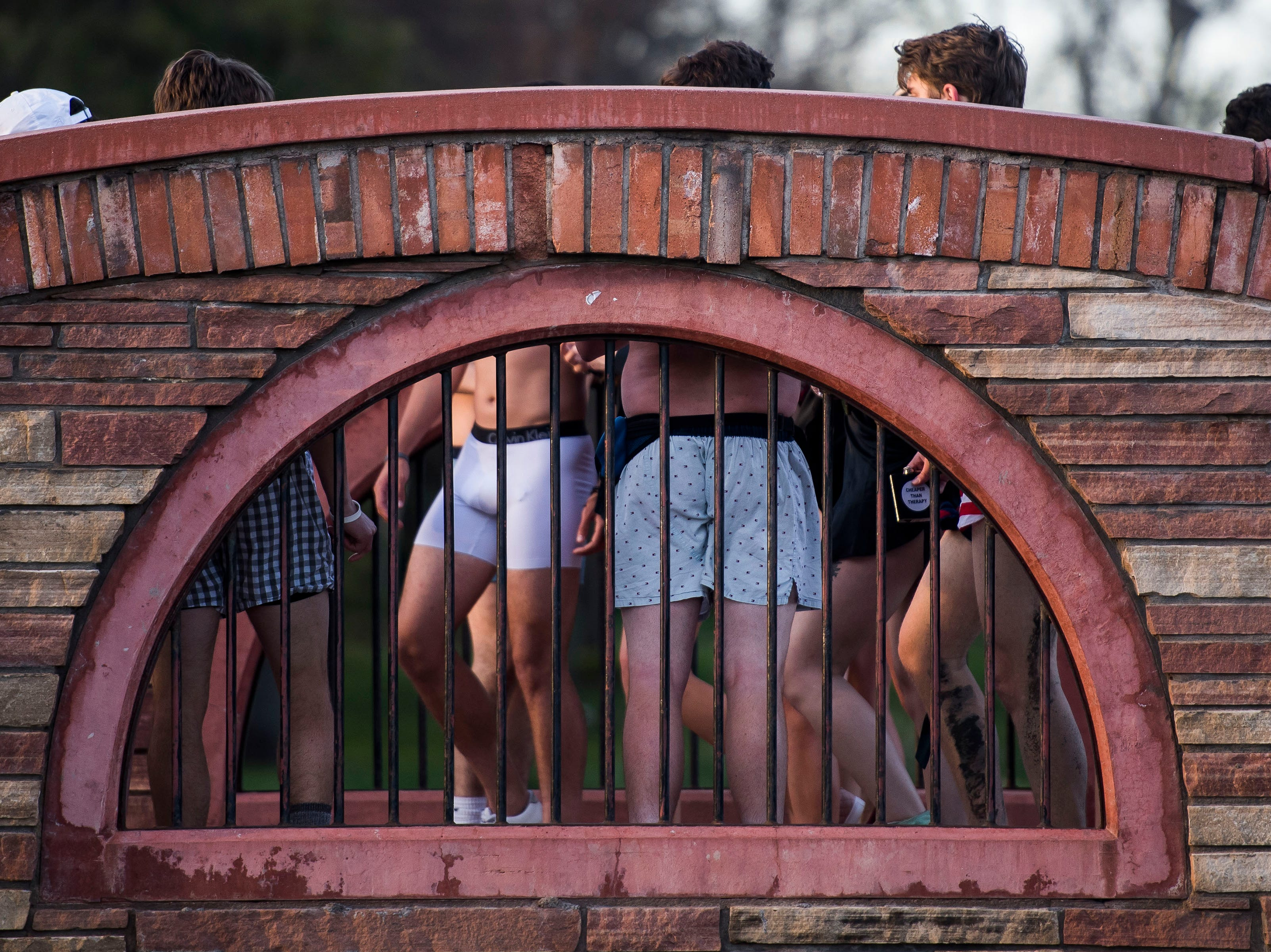 """Participants cross the bridge between the lagoon and the recreation center during the """"Undie Run"""" on Friday, May 10, 2019, on the Colorado State University campus in Fort Collins, Colo."""