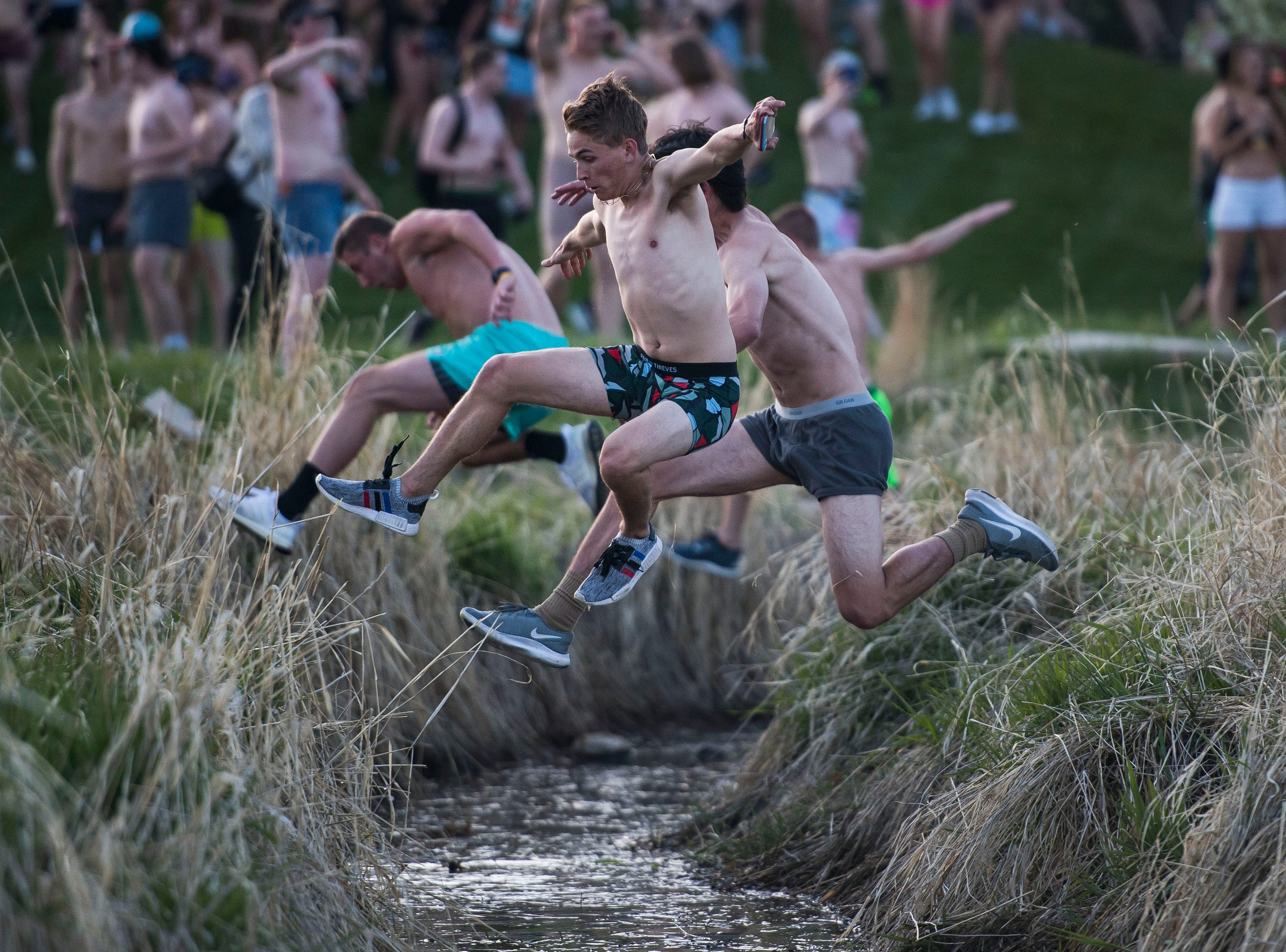 """Participants leap over the ditch near the recreation center during the """"Undie Run"""" on Friday, May 10, 2019, on the Colorado State University campus in Fort Collins, Colo."""