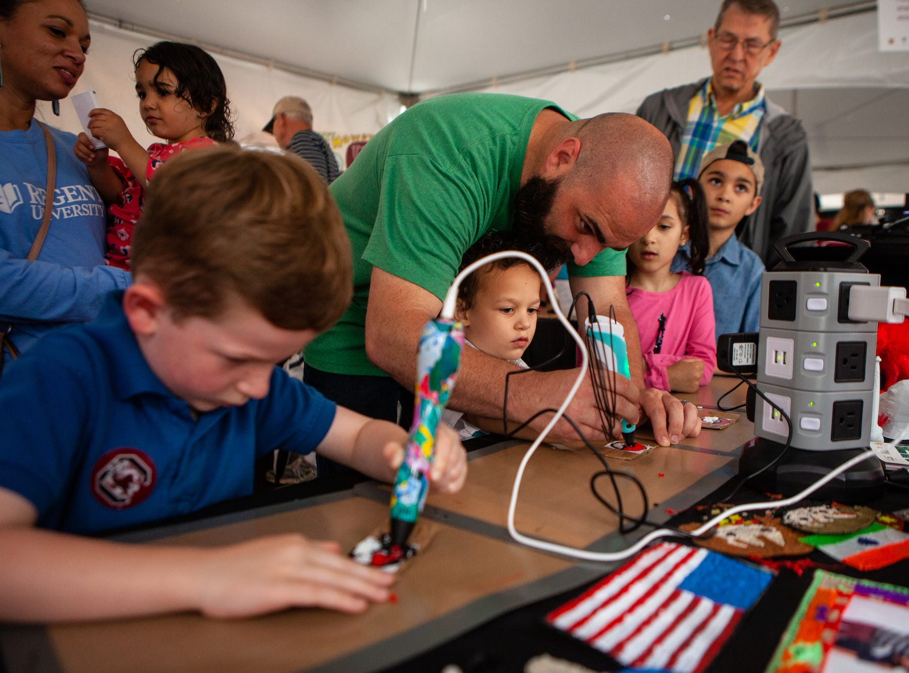 Joshua Thomas and his son, Nehemiah, 4, create art with a handheld 3D printer by Artistphere in Greenville on Saturday, May 11, 2019.