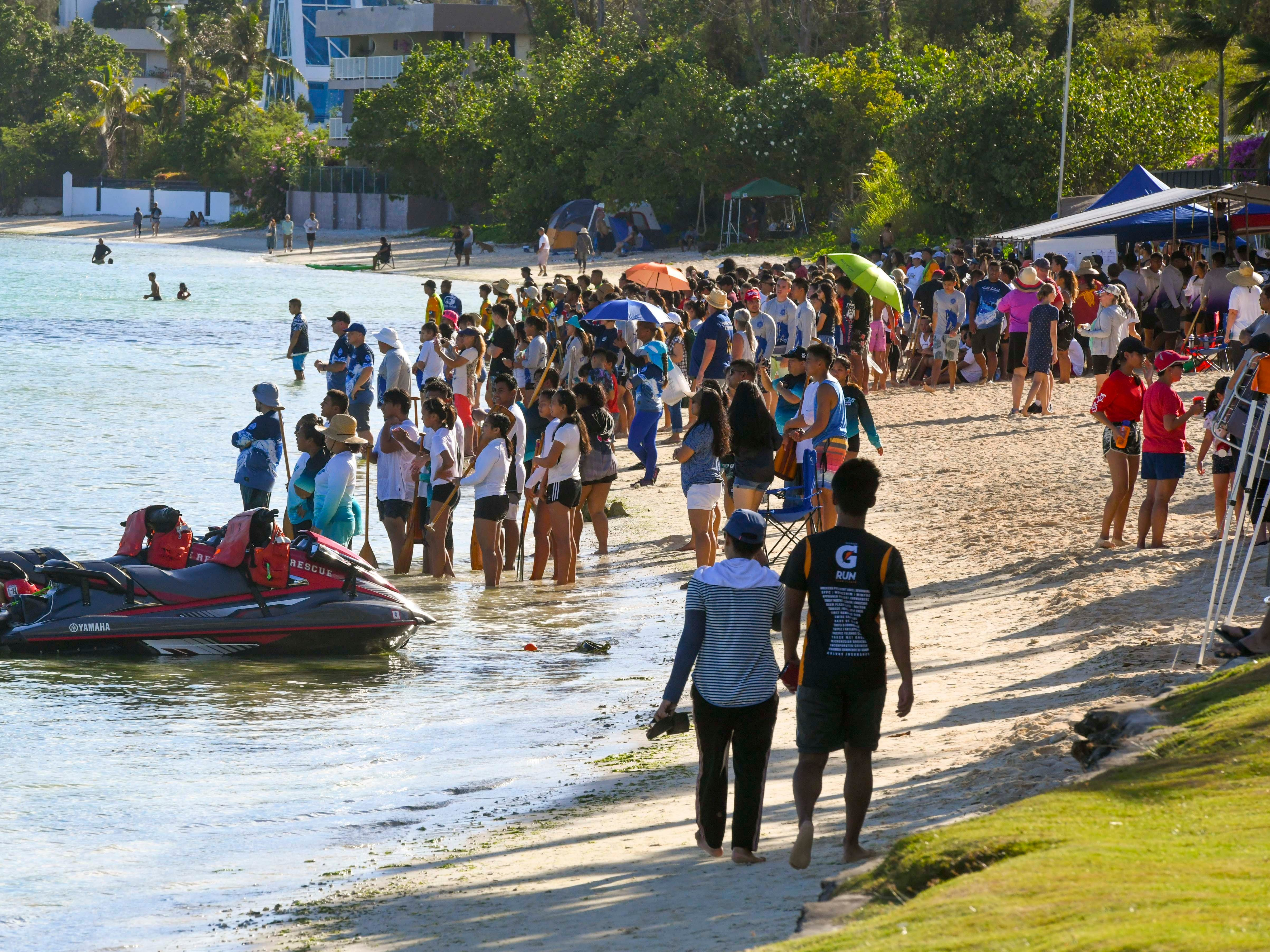 Cheers are projected from the shore by fellow student as high school paddling teams push their canoes through the waters off Matapang Beach during IIAAG Paddling competition preliminary races in Tumon on Saturday, May 11, 2019.
