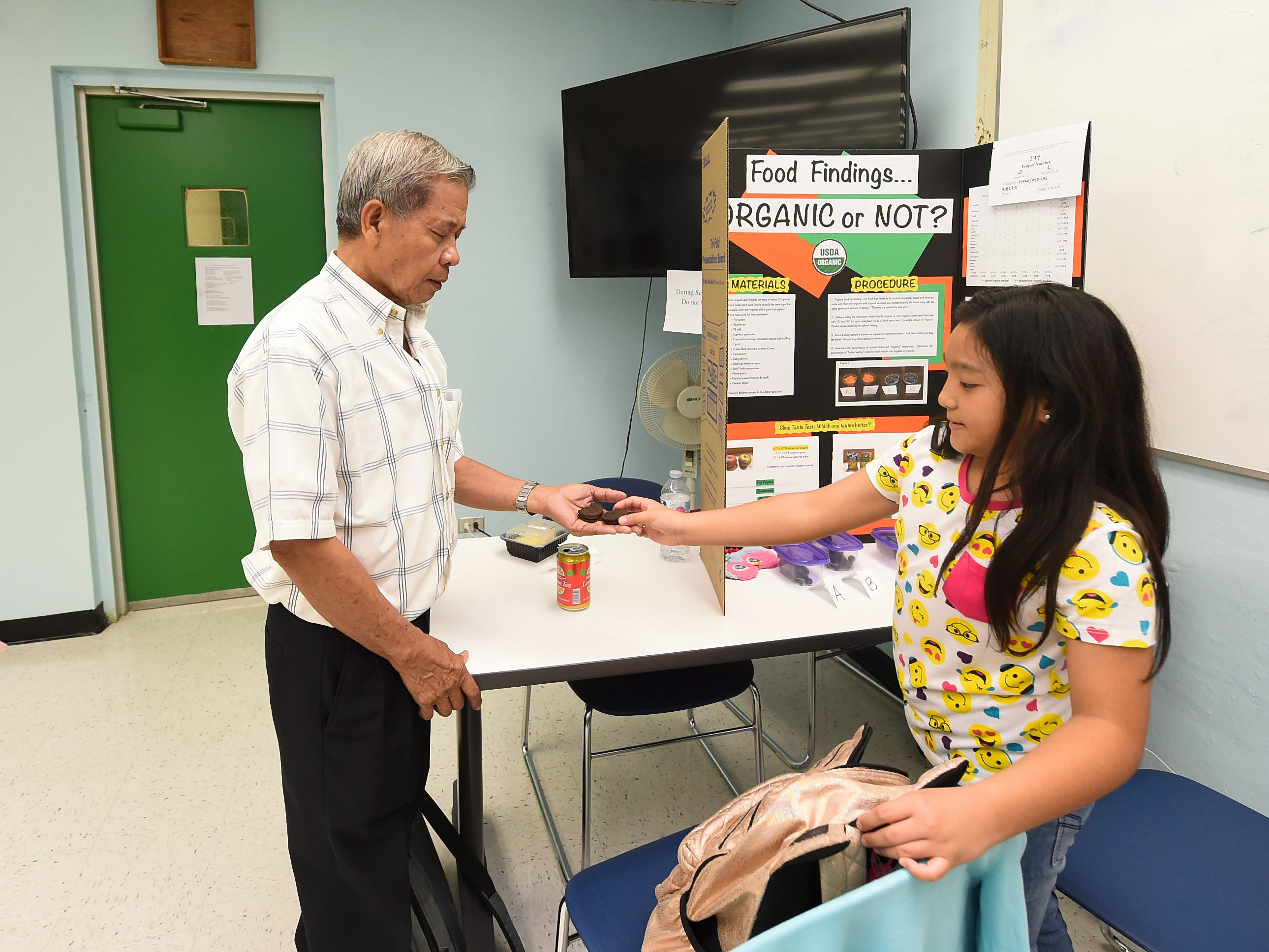 Mika Borja, 9, uses Chief Brody Elementary School second-grade teacher, Juanito Nuevo, as a subject for her taste-test project during the 41st Annual Islandwide Science Fair at the University of Guam in Mangilao, May 11, 2019.