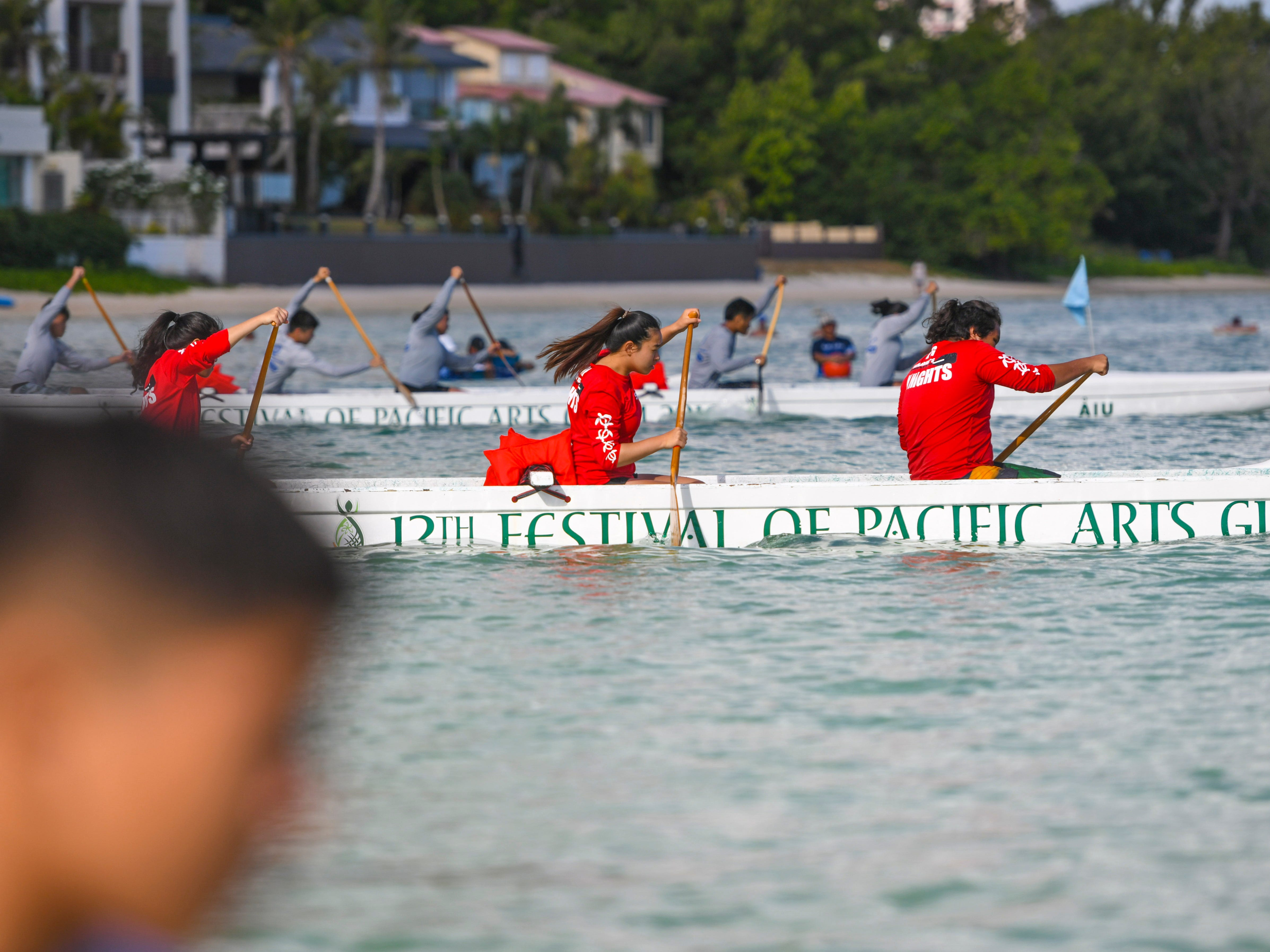 A St. John's Knight paddling team pushes away from the starting line as they compete in an IIAAG Paddling competition preliminary race against other teams in Tumon on Saturday, May 11, 2019.