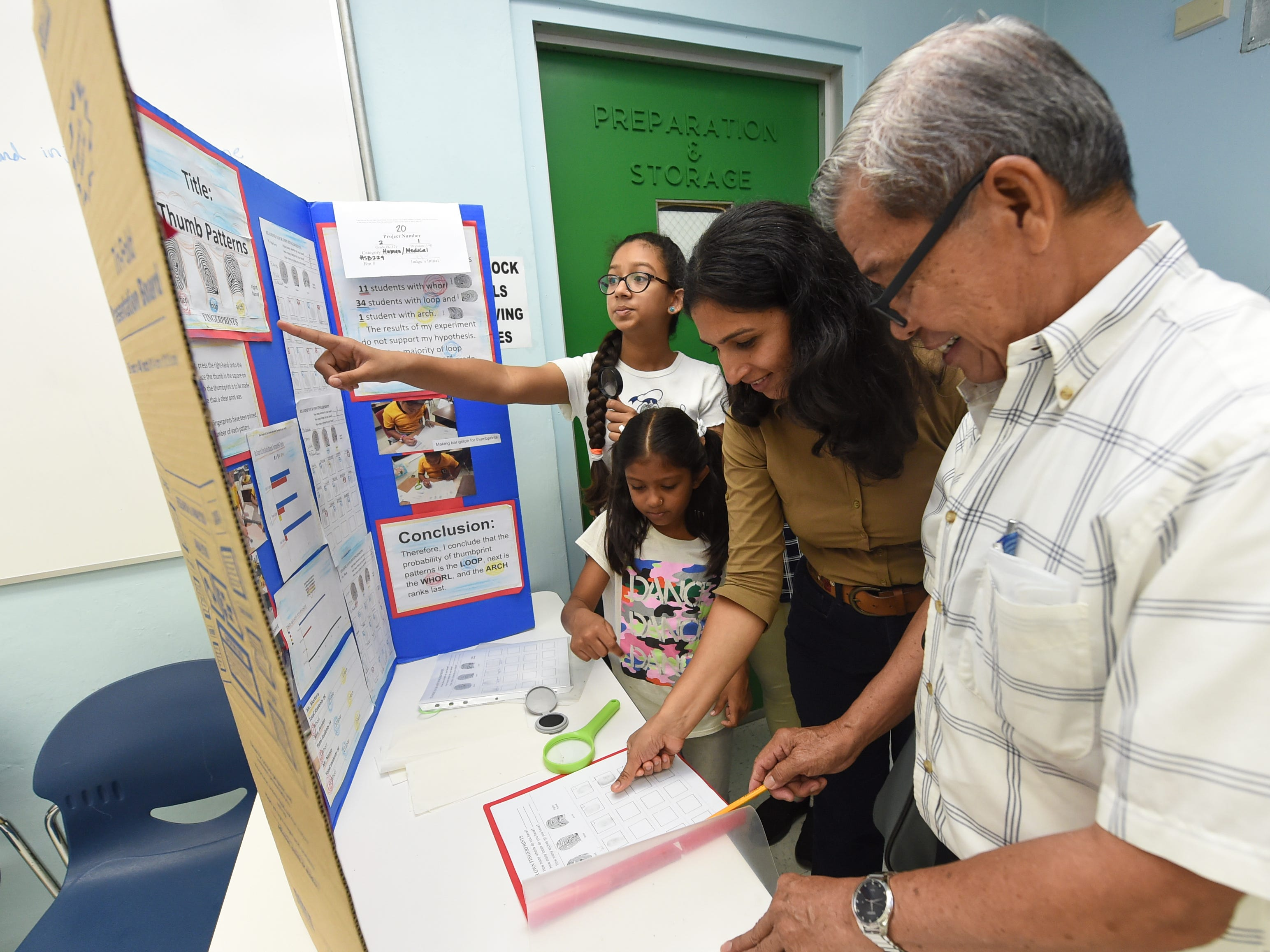 "Juanito Nuevo, a Chief Brody Elementary School teacher, right, shows off his student's ""Thumb Patterns"" science project to a family during the 41st Annual Islandwide Science Fair at the University of Guam in Mangilao, May 11, 2019."