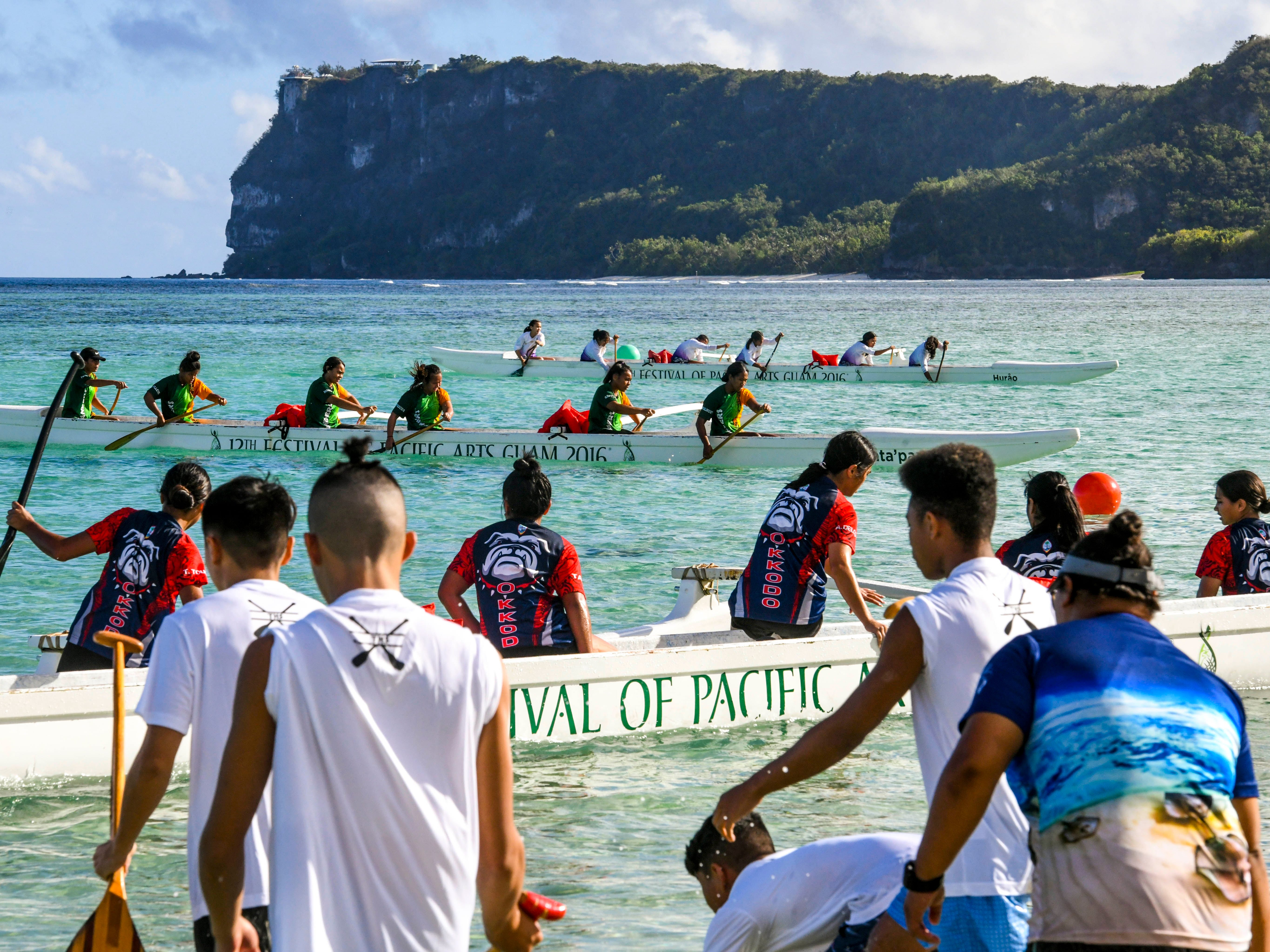 High school paddling teams push their canoes through the waters off Matapang Beach as they compete against each other in IIAAG Paddling competition preliminary races in Tumon on Saturday, May 11, 2019.