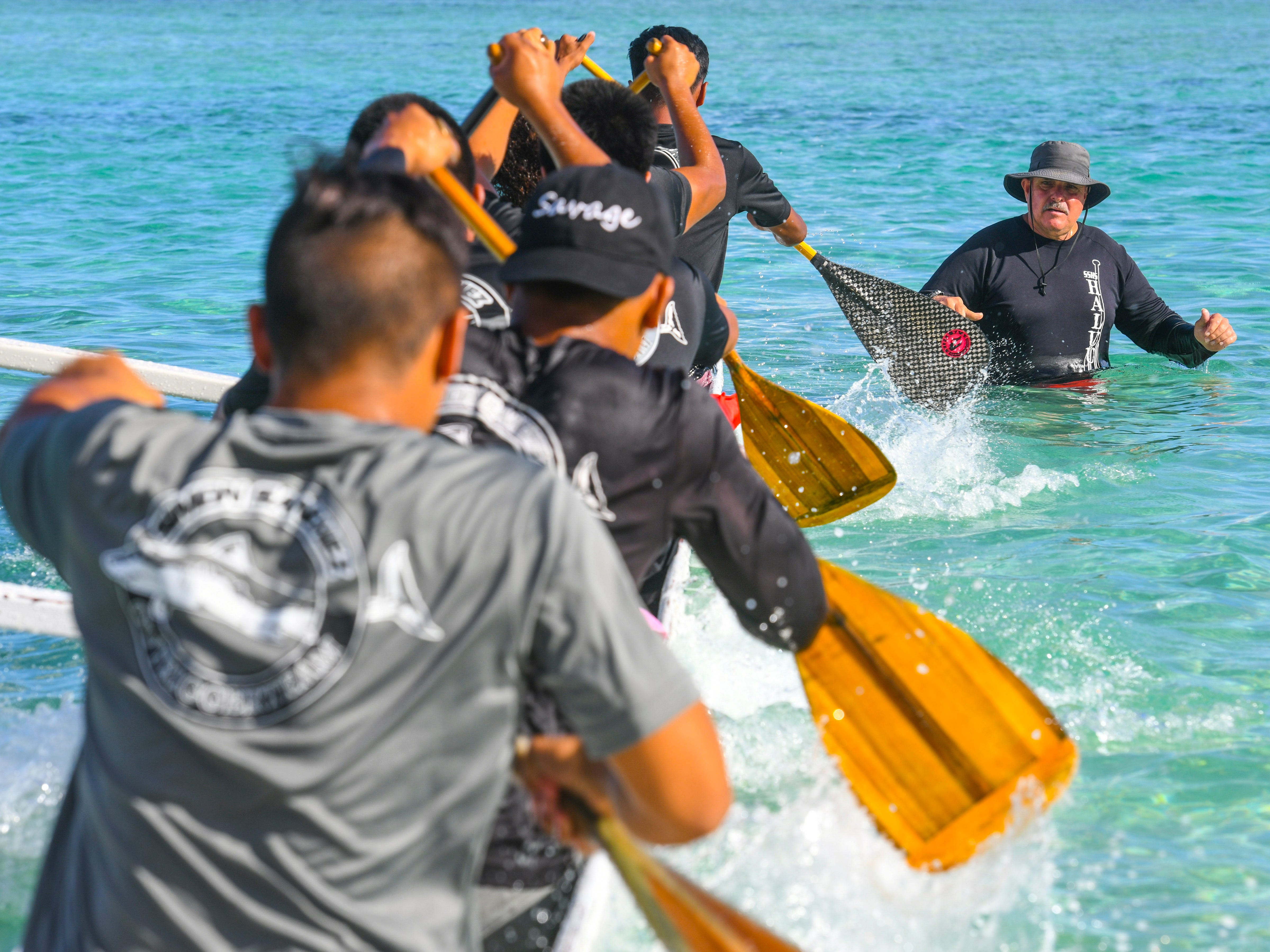 Simon Sanchez Shark's paddling coach Ron Ruiz clears from the bow of his team's canoe as they kick off from the starting line during a 1000m mixed manhoben preliminary race in IIAAG Paddling competition at Matapang Beach in Tumon on Saturday, May 11, 2019.