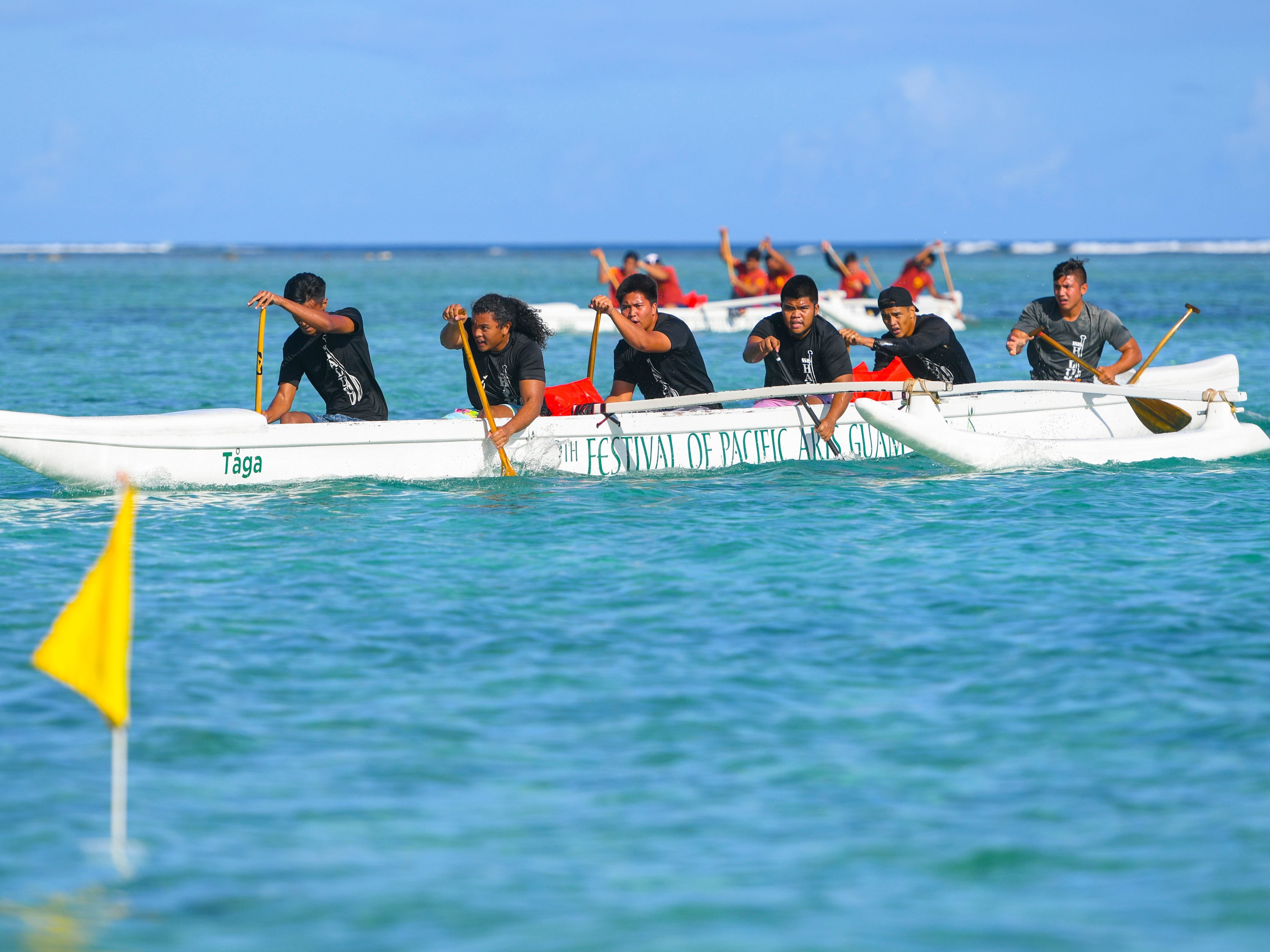 Simon Sanchez Shark paddlers focus their attention on the finish line during a 1000m mixed manhoben preliminary race in IIAAG Paddling competition at Matapang Beach in Tumon on Saturday, May 11, 2019.