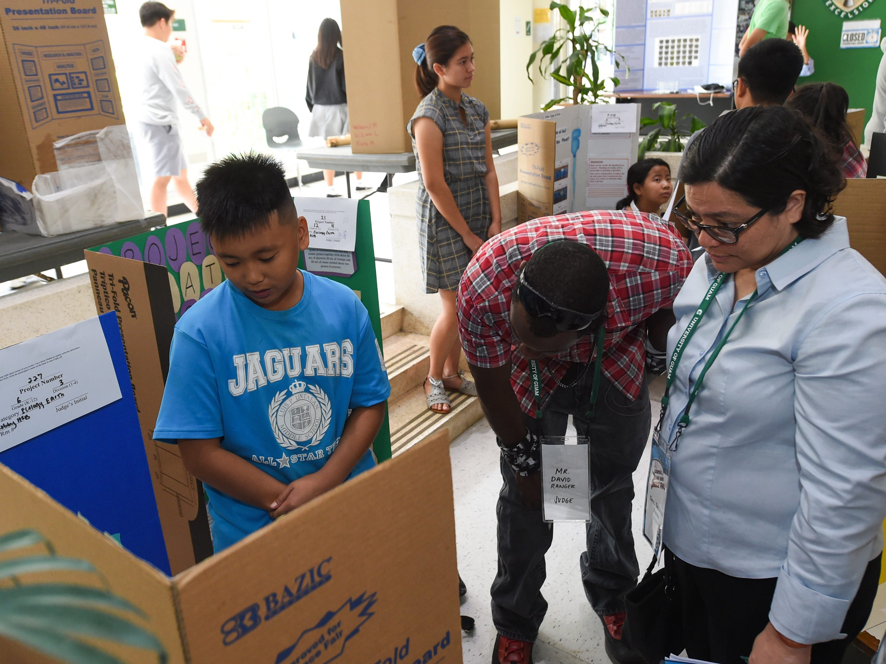 Sixth grader James Ceria, 11, explains his project to judges David Ranger and Sen. Sabina Perez during the 41st Annual Islandwide Science Fair at the University of Guam in Mangilao, May 11, 2019.