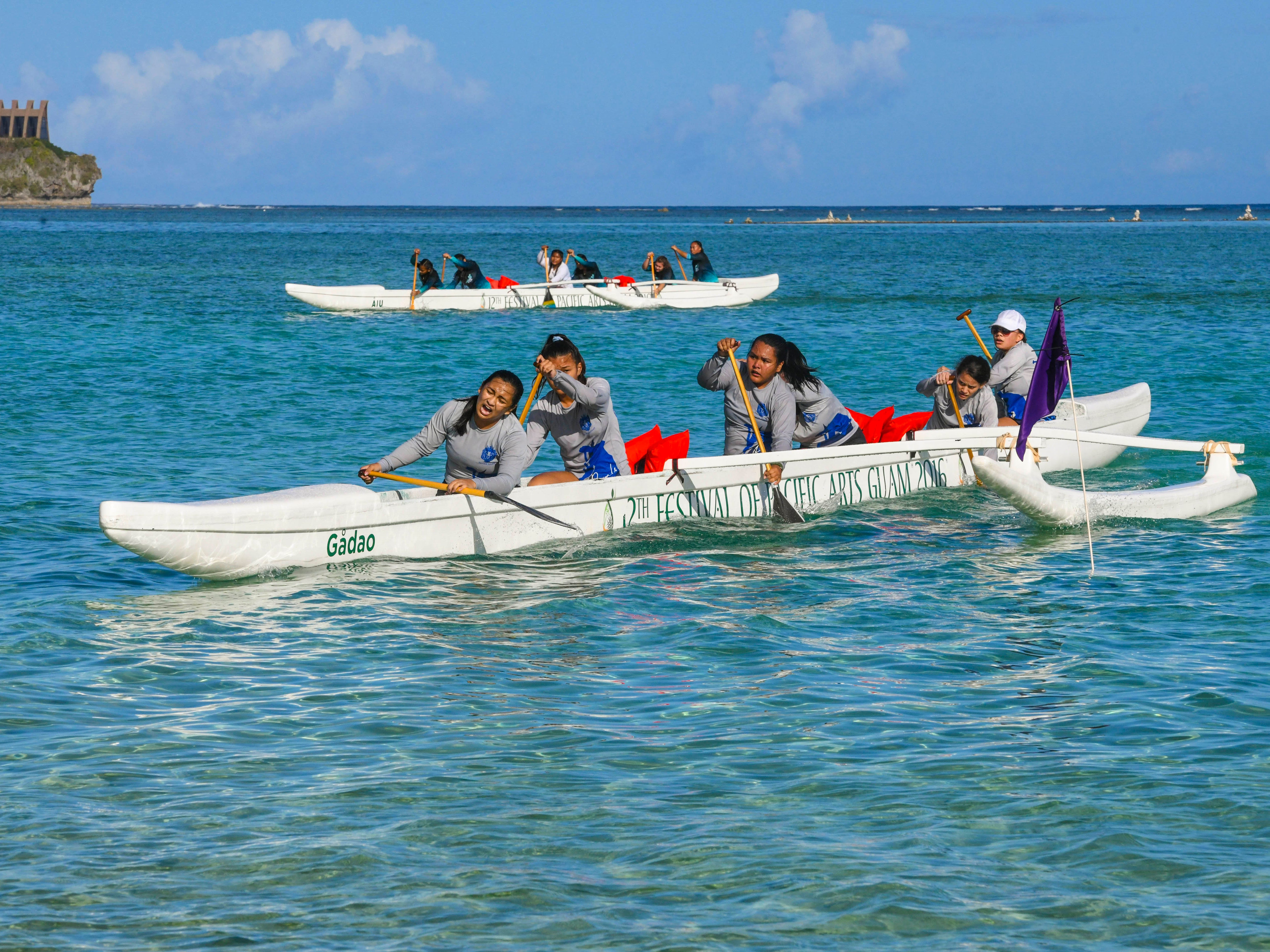 Paddlers from Notre Dame School glide pass the finish line after completing a race against other teams in an IIAAG Paddling competition preliminary race held at Matapang Beach in Tumon on Saturday, May 11, 2019.