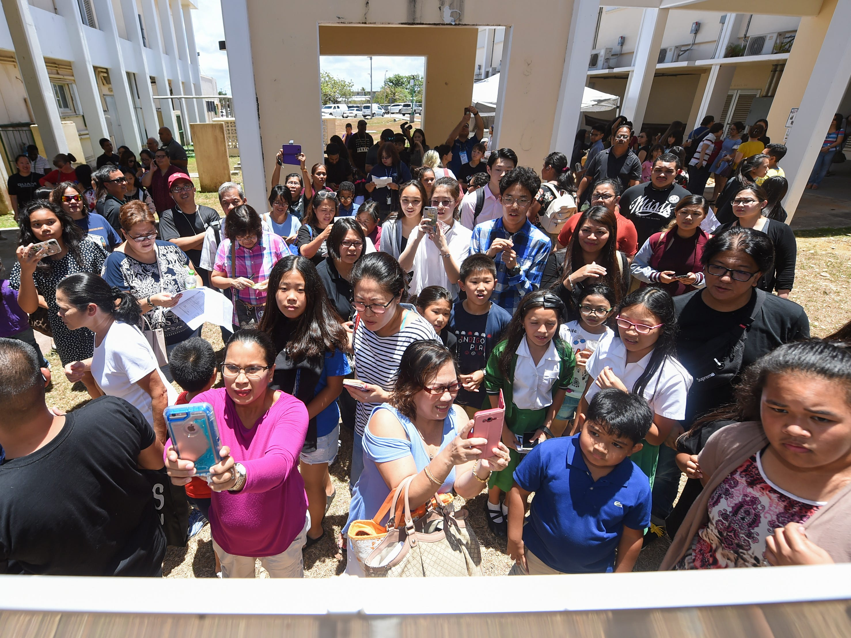 Families and science fair participants gather around a marker board to view results for the 41st Annual Islandwide Science Fair at the University of Guam in Mangilao, May 11, 2019.