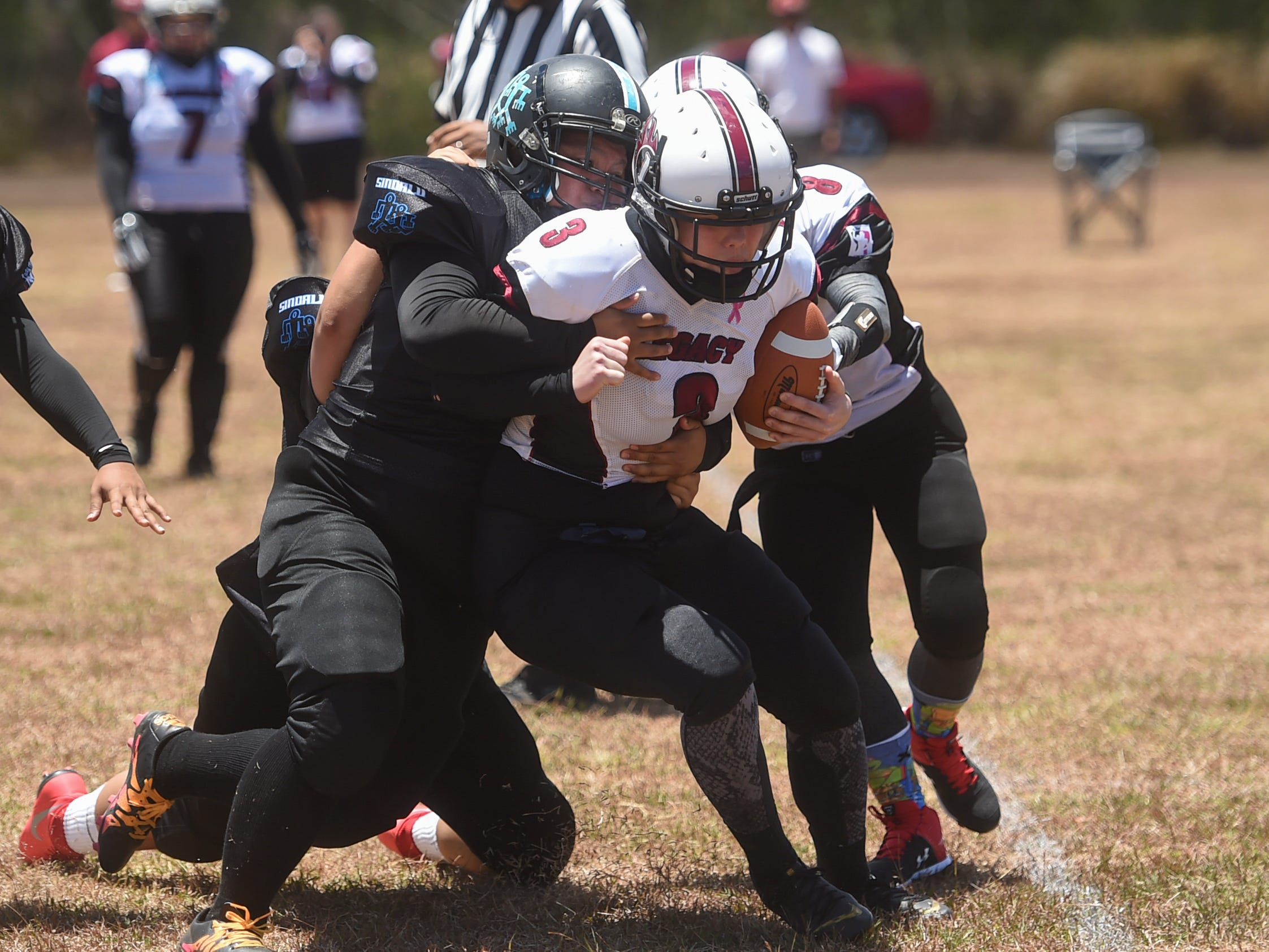 The Sindalu/Raiders' defense takes down Legacy quarterback Kalanie Martinez (8) during their 2019 Bud Light GWTFL game at the University of Guam Field in Mangilao, May 11, 2019. Legacy came away with a 20-0 victory for their second game of the season.