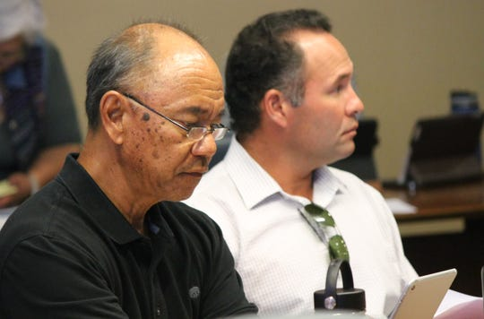 Condolidated Commission on Utilities members Simon Sanchez, left, and Mike Limtiaco, attend a May 10 commission meeting, during which commissioners voted unanimously to rescind pay raises they approved last November.