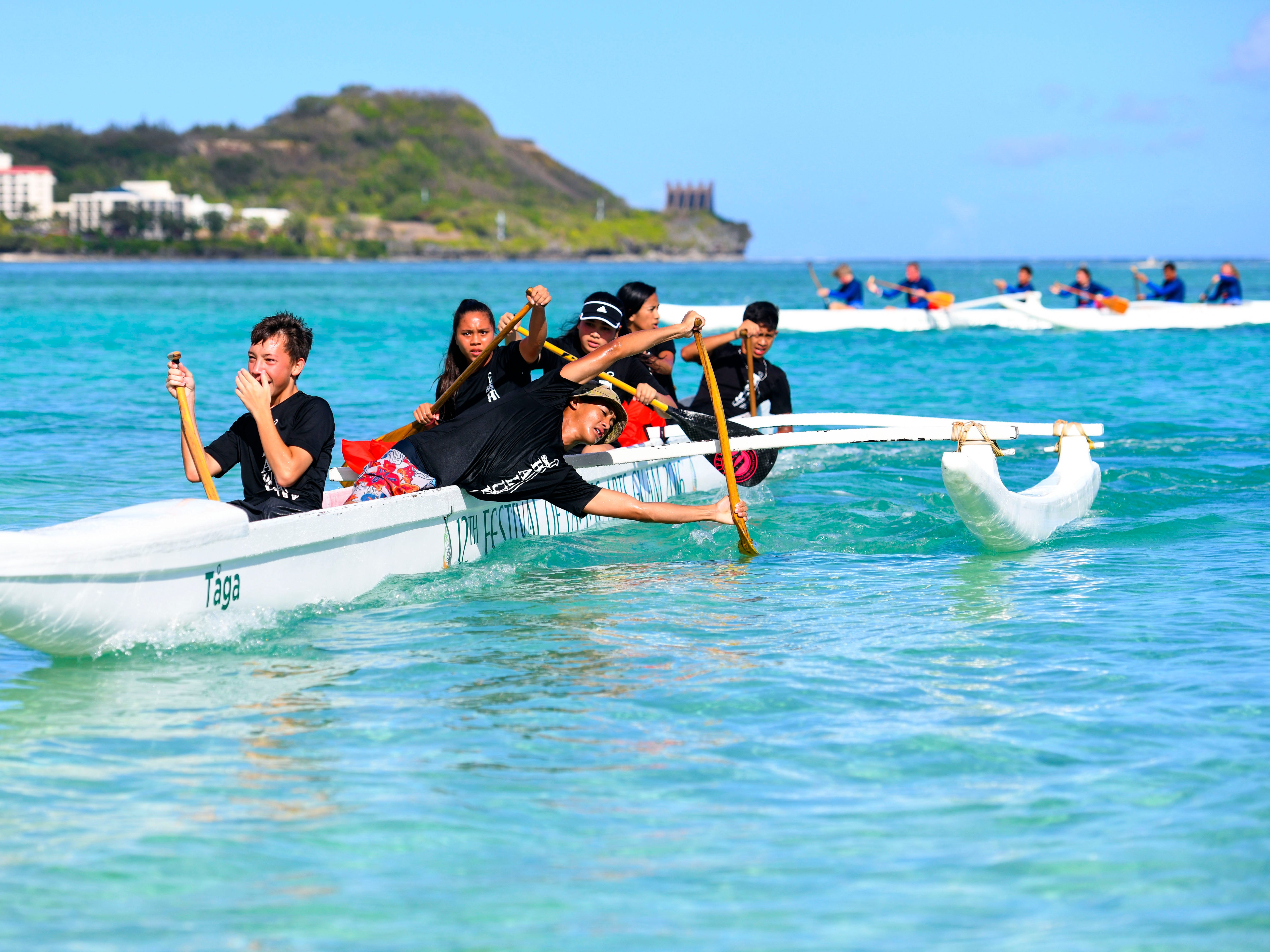 Simon Sanchez Shark paddlers cross the finish line after completing a 1000m mixed manhoben preliminary race in IIAAG Paddling competition at Matapang Beach in Tumon on Saturday, May 11, 2019.