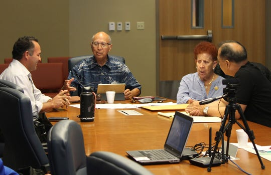 From left, Consolidated Commission on Utilities member Mike Limtiaco, Chairman Joseph Duenas, member Judith Guthertz, and attorney Vincent Leon Guerrero chat before the May 10 commission meeting related to management pay raises and bonuses.